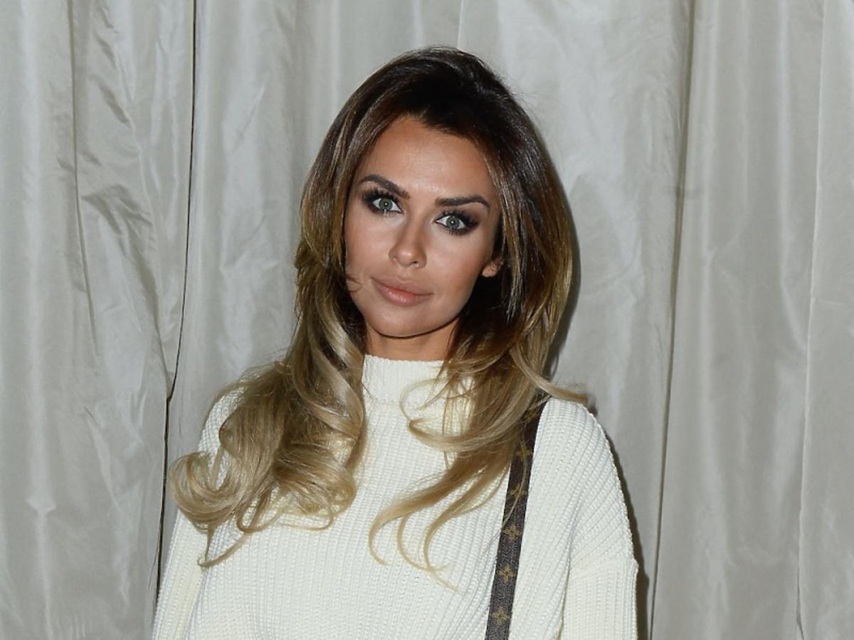 Natali Siwiec w białym swetrze, szarych kozakach z paskiem i torbą na pasku Louis Vuitton