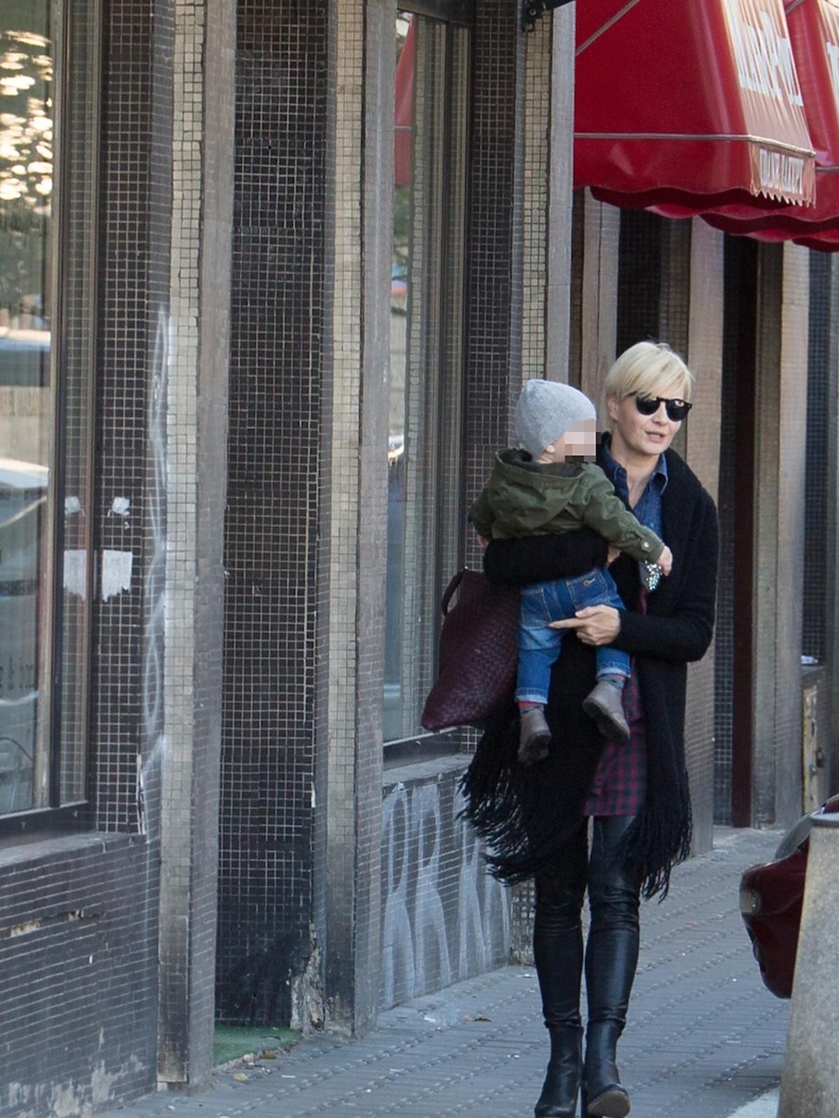 Małgorzata Kożuchowska w zielonej kurtce i czarnych spodniach na ulicy z synkiem na rękach