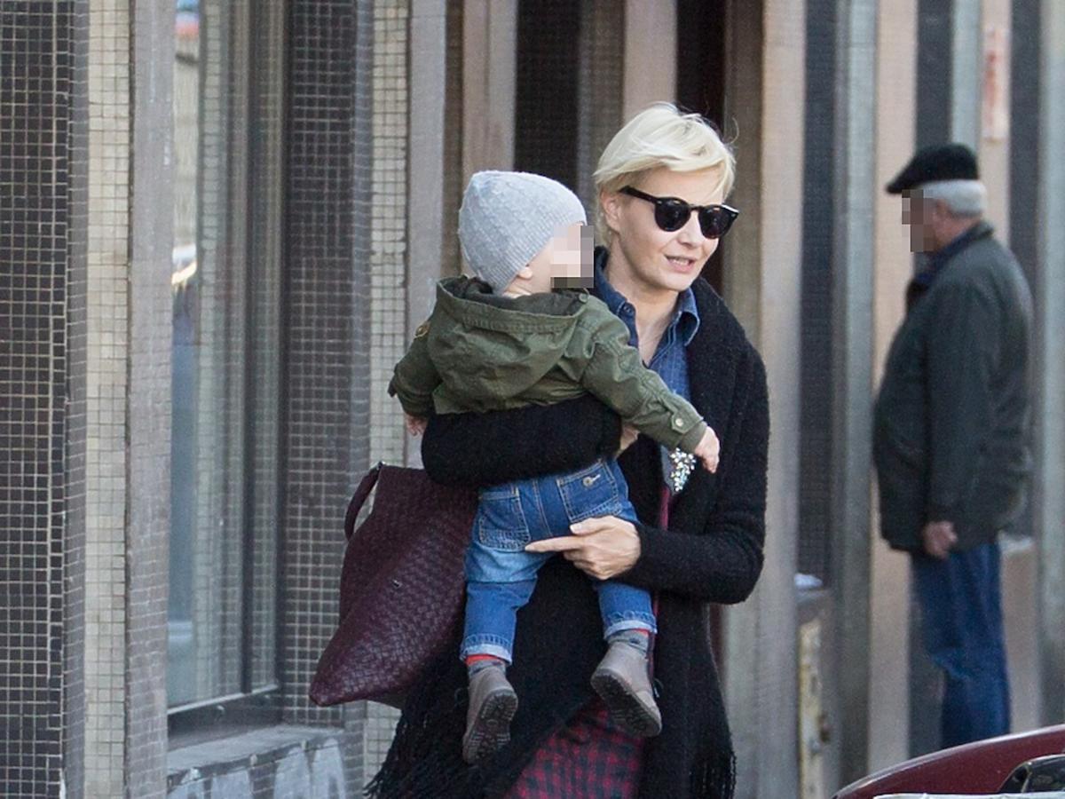 Małgorzata Kożuchowska w ciemnych okularach z synem na rękach idzie ulicą
