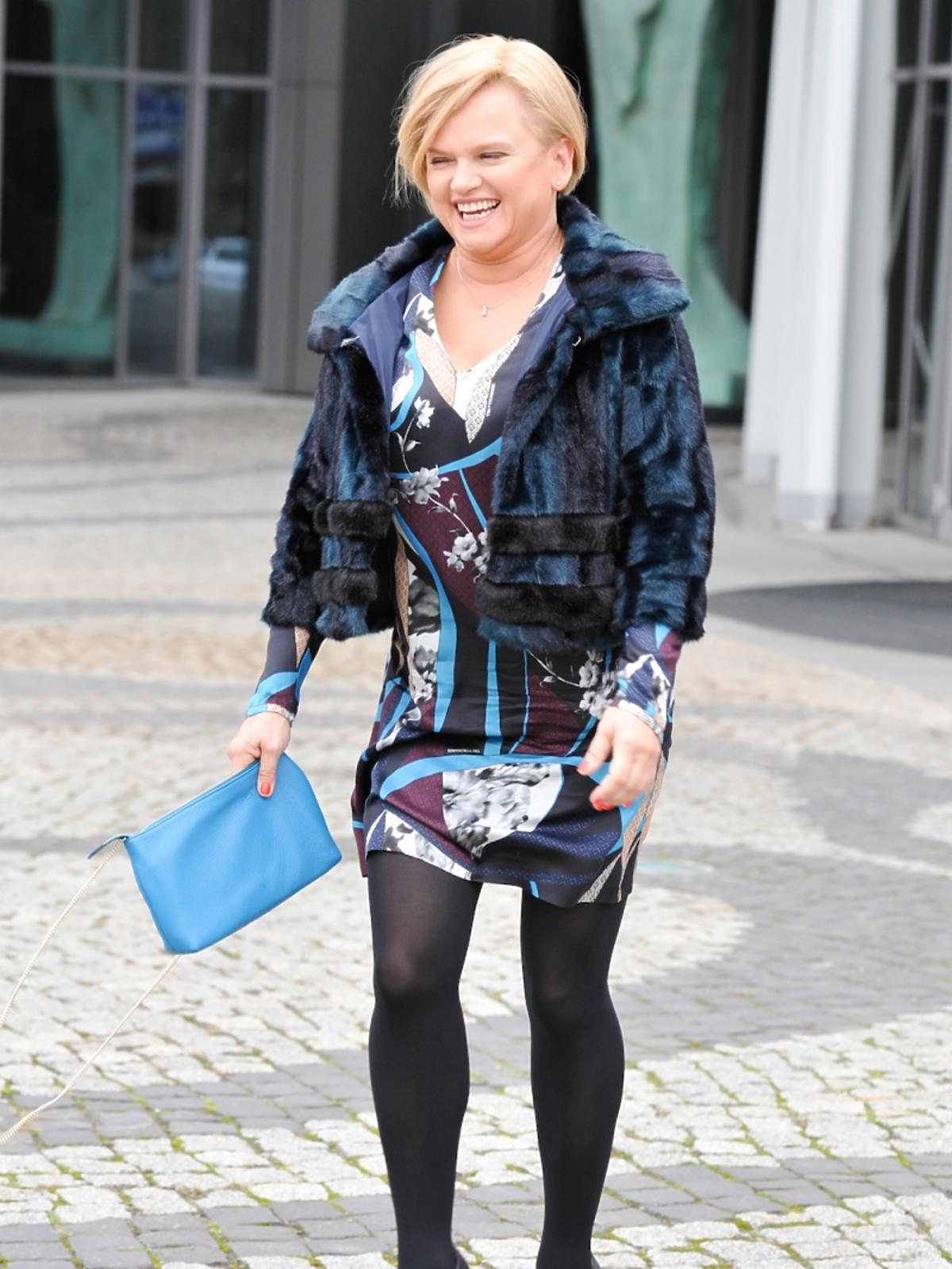 Katarzyna Figura w sukience w printy, kolorowym futerku, czarnych szpilkach i rajstopach, niebieską torebką