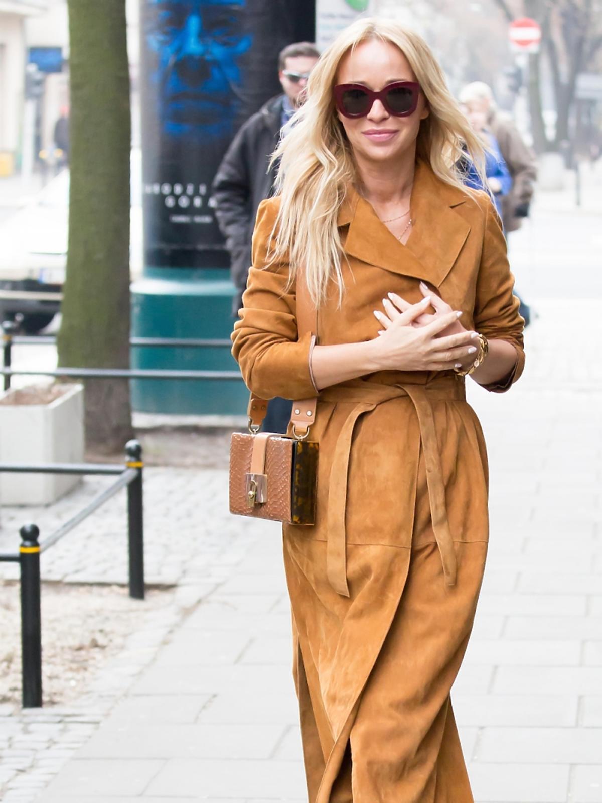 Joanna Przetakiewicz w brązowym zamszowym płaszczu, dżinsach, dużych okularach, małą brązową torebką