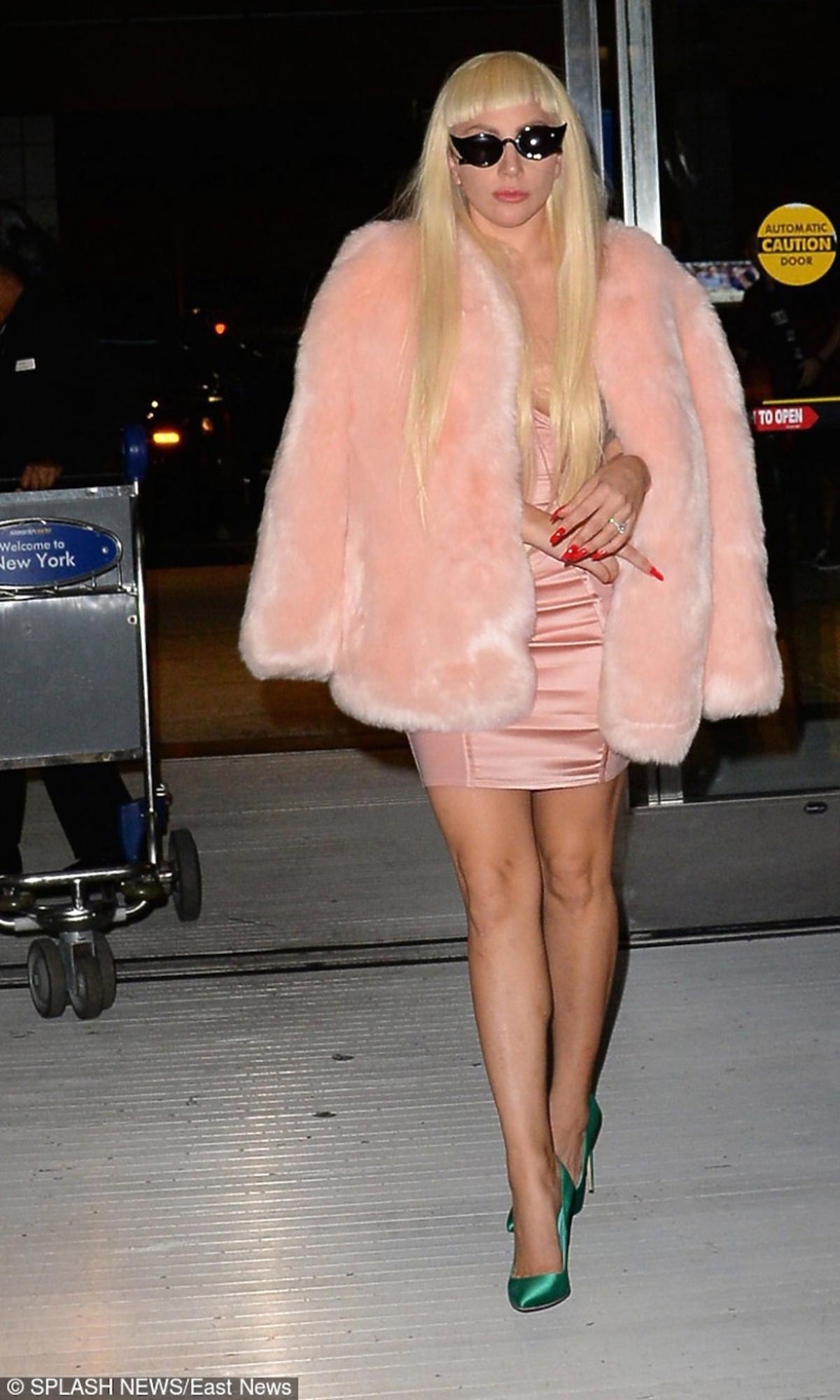Lady Gaga w jasno różowej sukience, futerku, zielonych szpilkach, czarnych okularach
