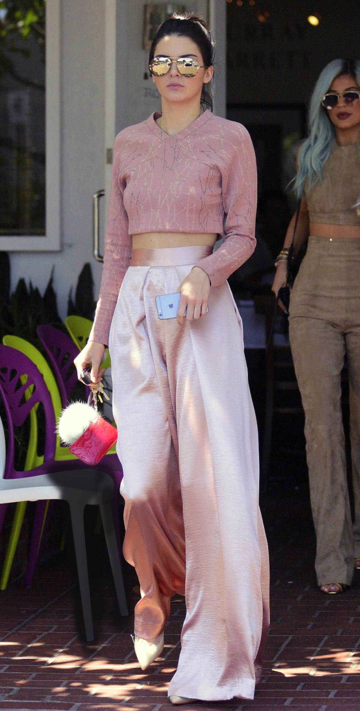 Kendall Jenner w różowych szerokich spodniach, crop-bluzce, okularach lustrzankach