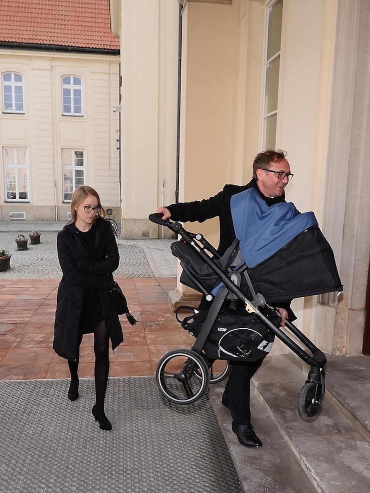 Andrzej Chyra z synkiem w niebieskim wózku i partnerką Pauliną przed ministerstwem kultury
