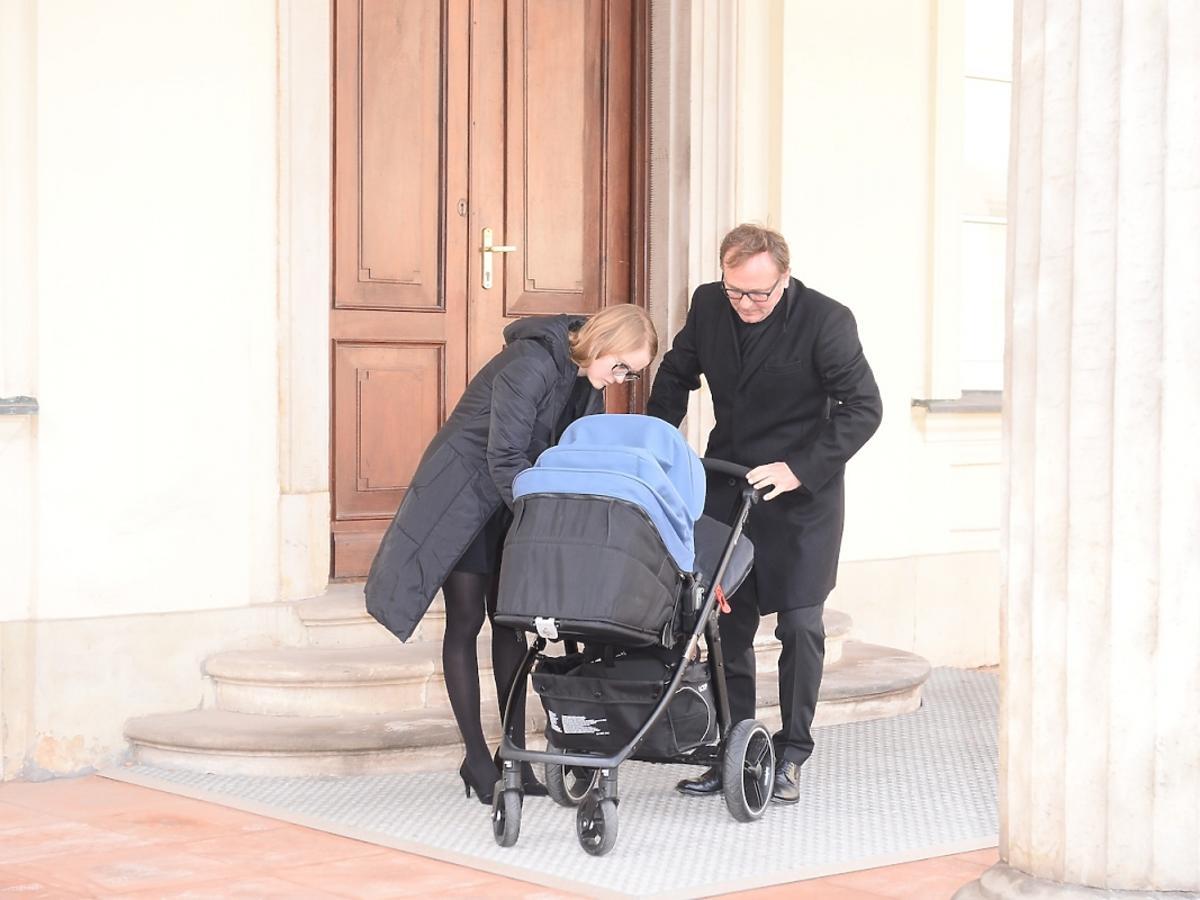 Andrzej Chyra w czarnym płaszczu z synkiem w niebieskim wózku i partnerką Pauliną przed ministerstwem