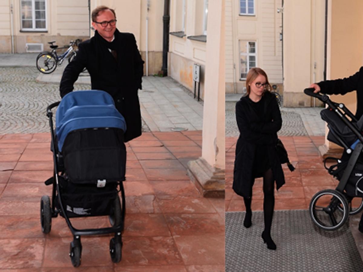Andrzej Chyra w czarnym płaszczu z synkiem w wózku i partnerką Pauliną przed ministerstwem