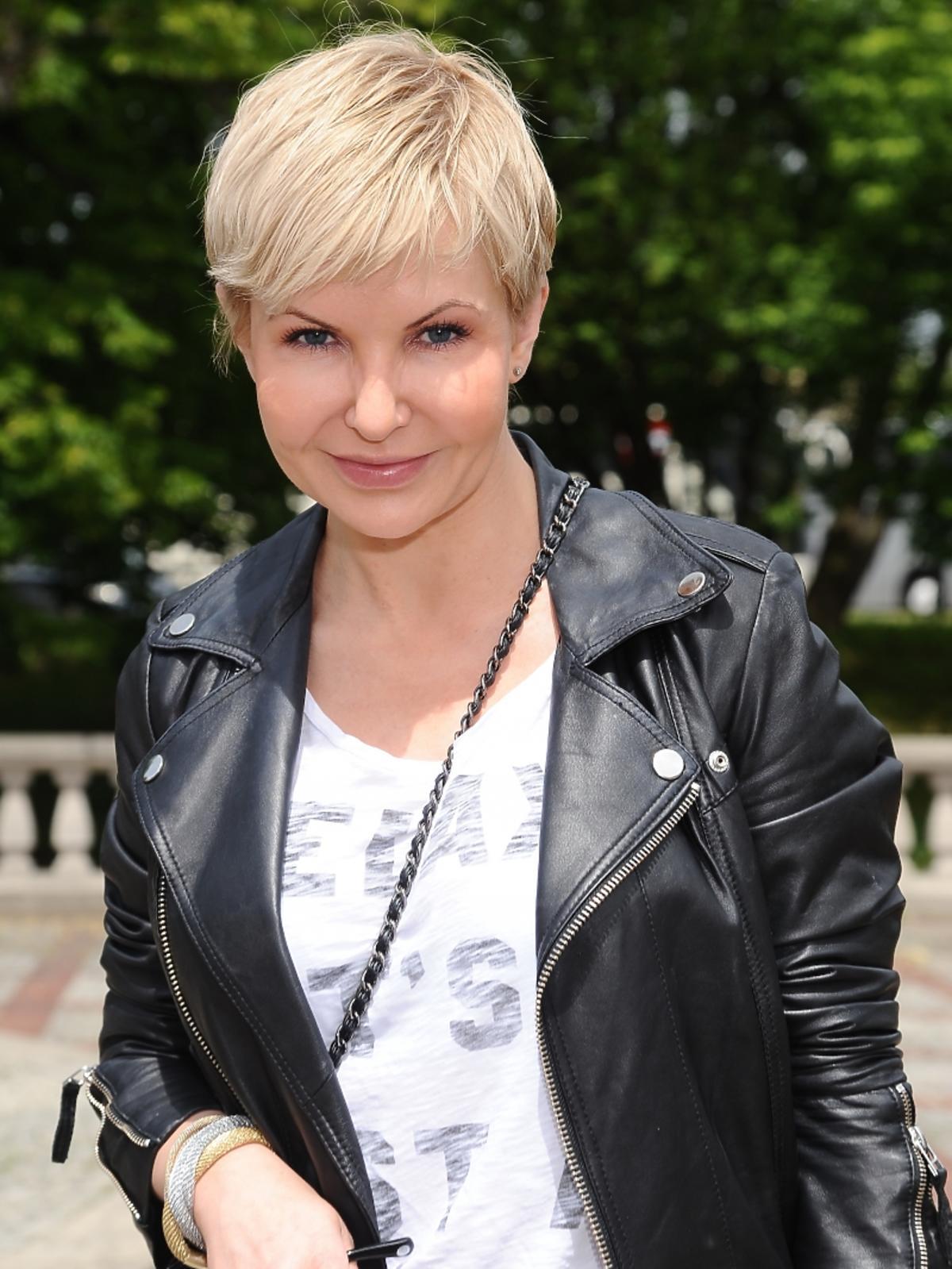Joanna Racewicz na zewnątrz w skórzanej kurtce i białej bluzce