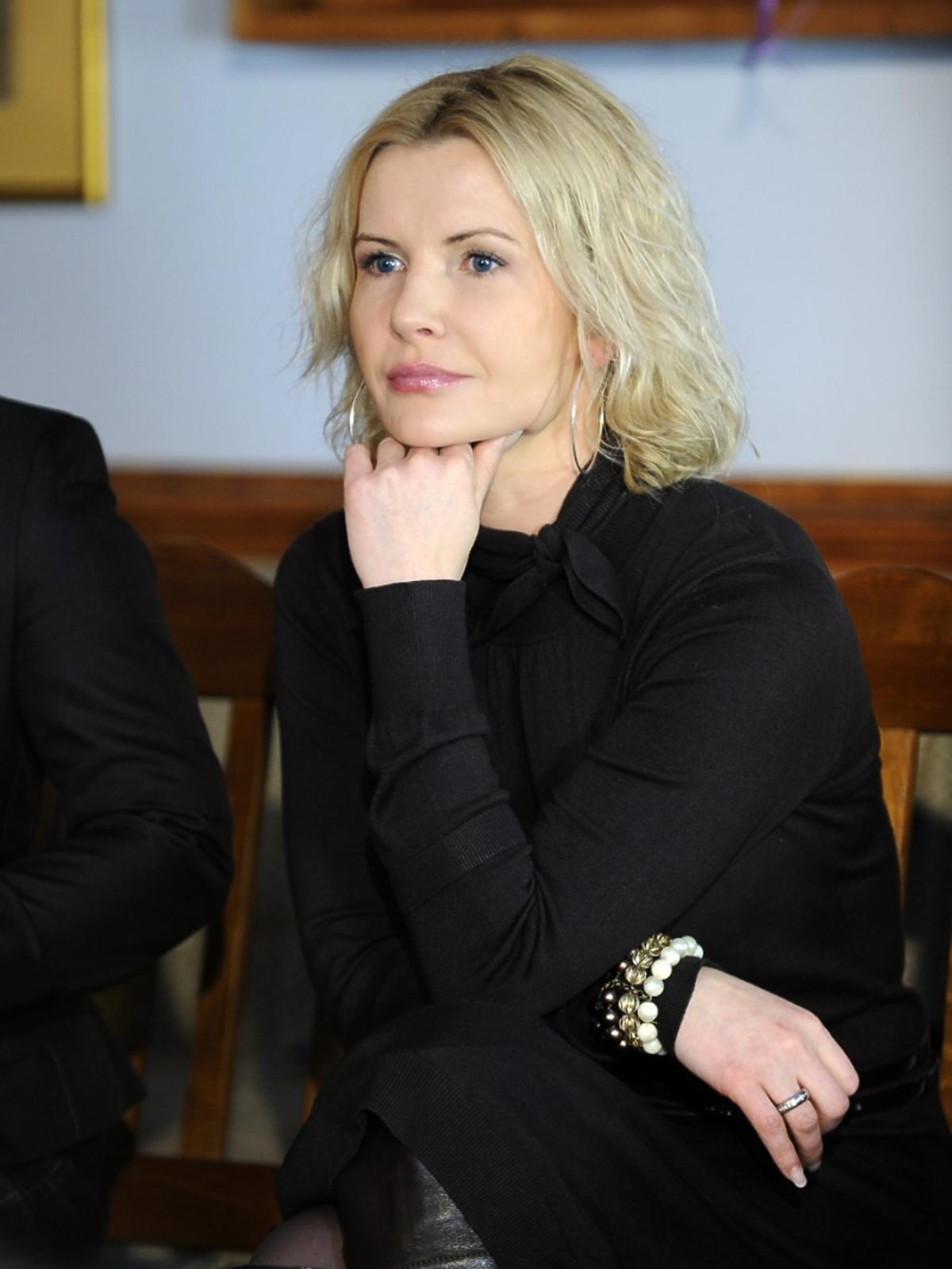 Joanna Racewicz w czarnej bluzce i spódnicy, zamyślona podpiera się ręką