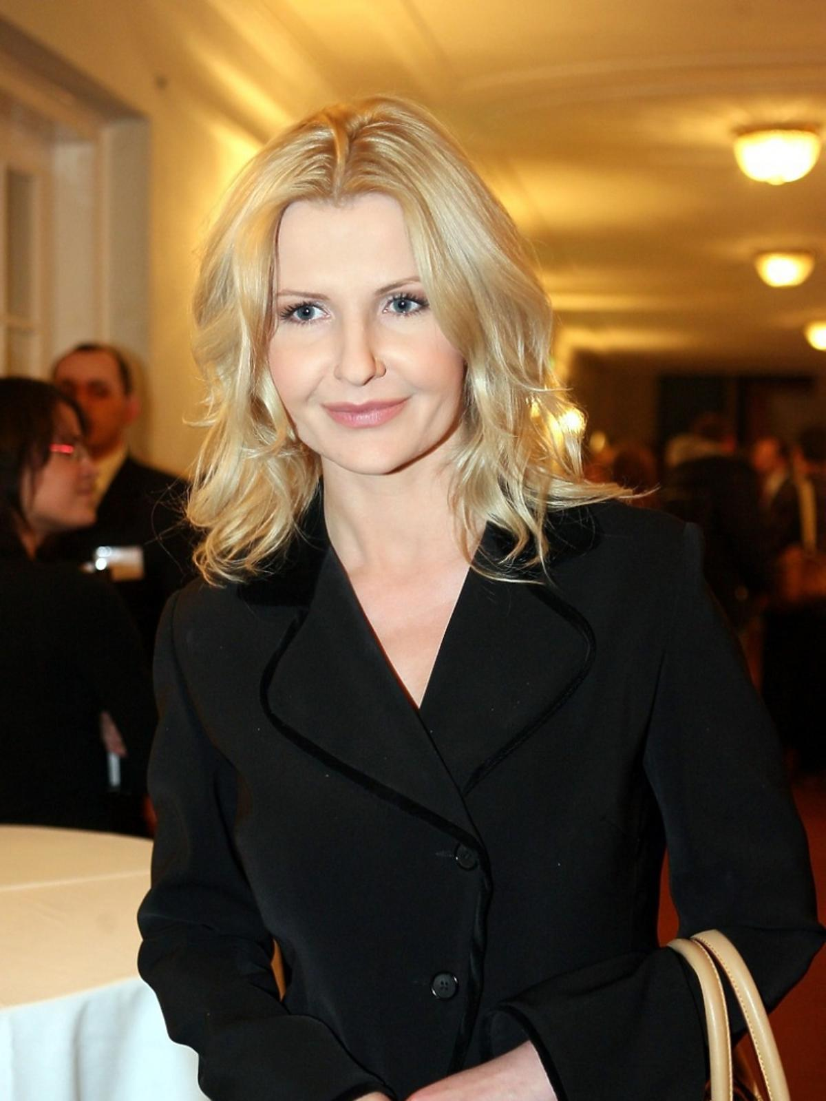 Joanna Racewicz półsylwetki stoi w czarnej sukience we  wnętrzu