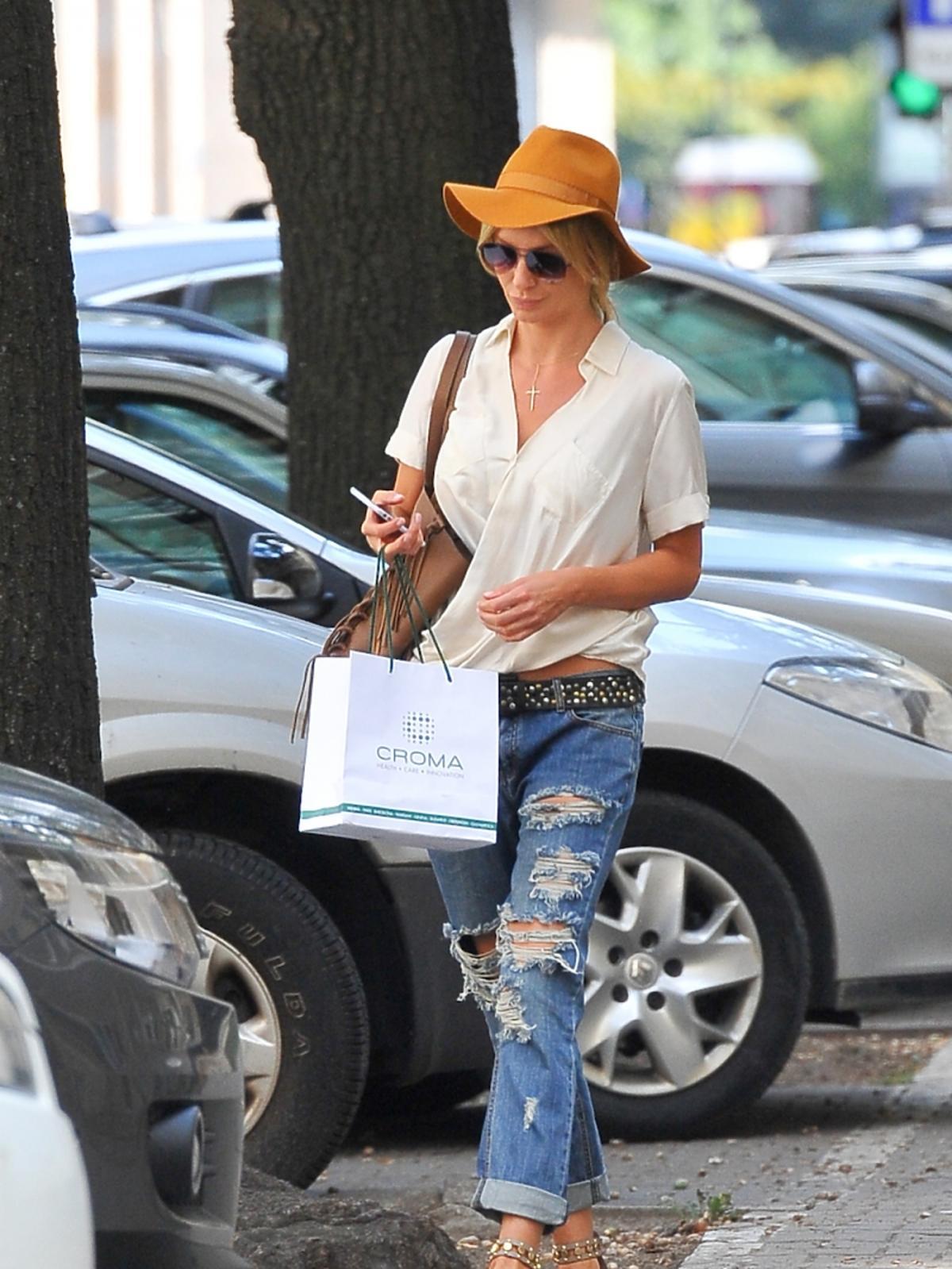 Agnieszka Szulim na ulicy w białej koszuli z kołnierzykiem i krótkim rękawem, poszarpanych dżinsach, sandałach, musztardowym kapeluszu