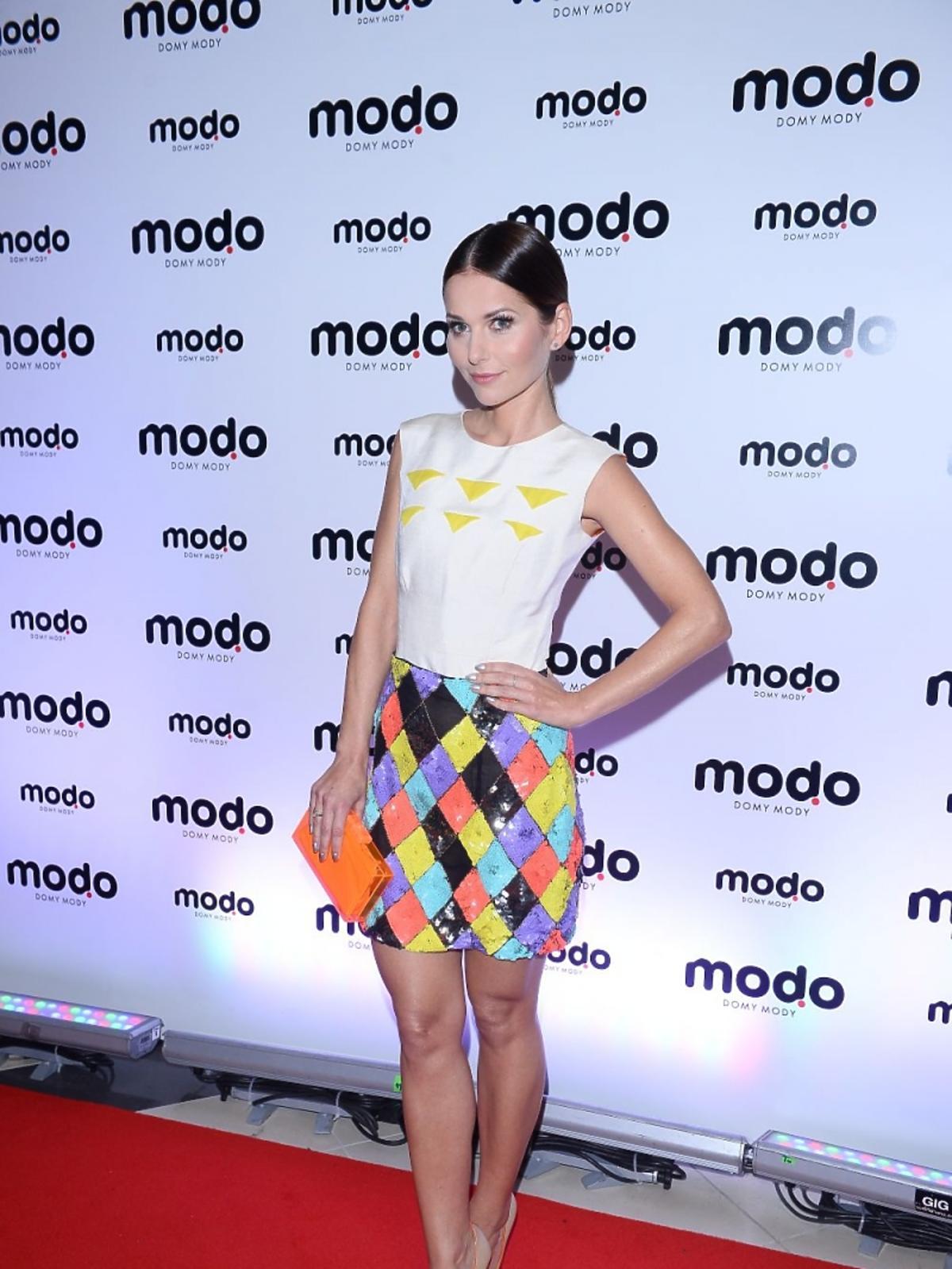 Paulina Sykut w białej bluzce i kolorowej geometrycznej spódnicy