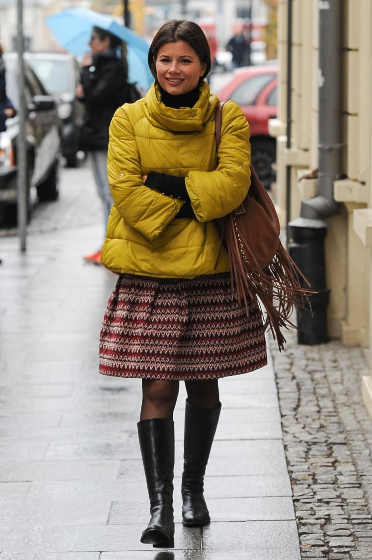 Agnieszka Sienkiewicz w żółtej kurtce i wysokich kozakach