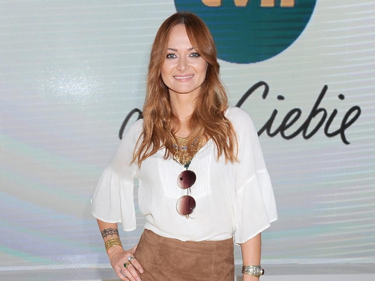 Anna Rusowiczw białej bluzce, brązowej spódnicy z frędzlami, brązowych sandałach  na szpilce, z etniczną biżuterią