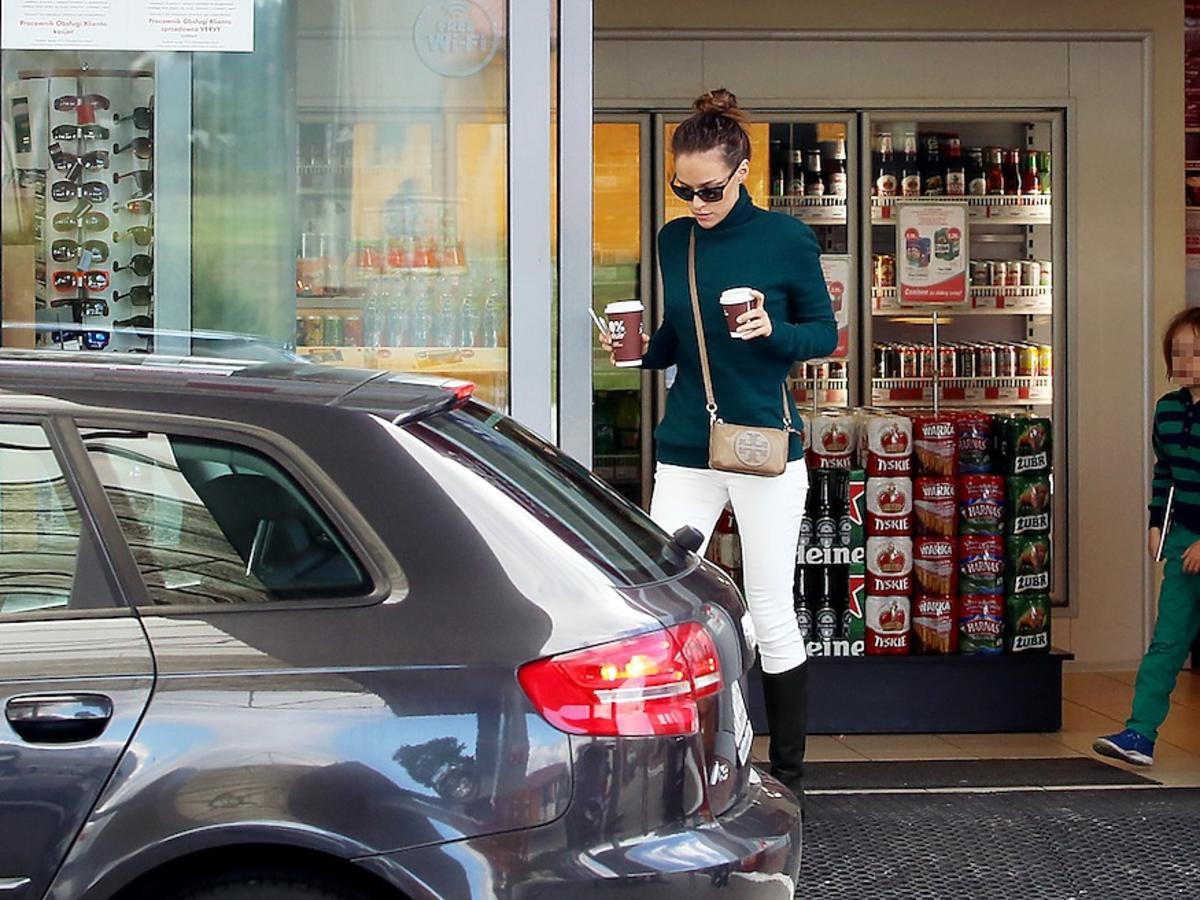 Alicja Bachleda-Curuś w białych spodniach i czarnych kozakach z synem na stacji benzynowej