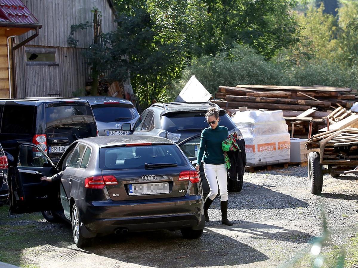 Alicja Bachleda-Curuś w białych spodniach i czarnych kozakach na parkingu