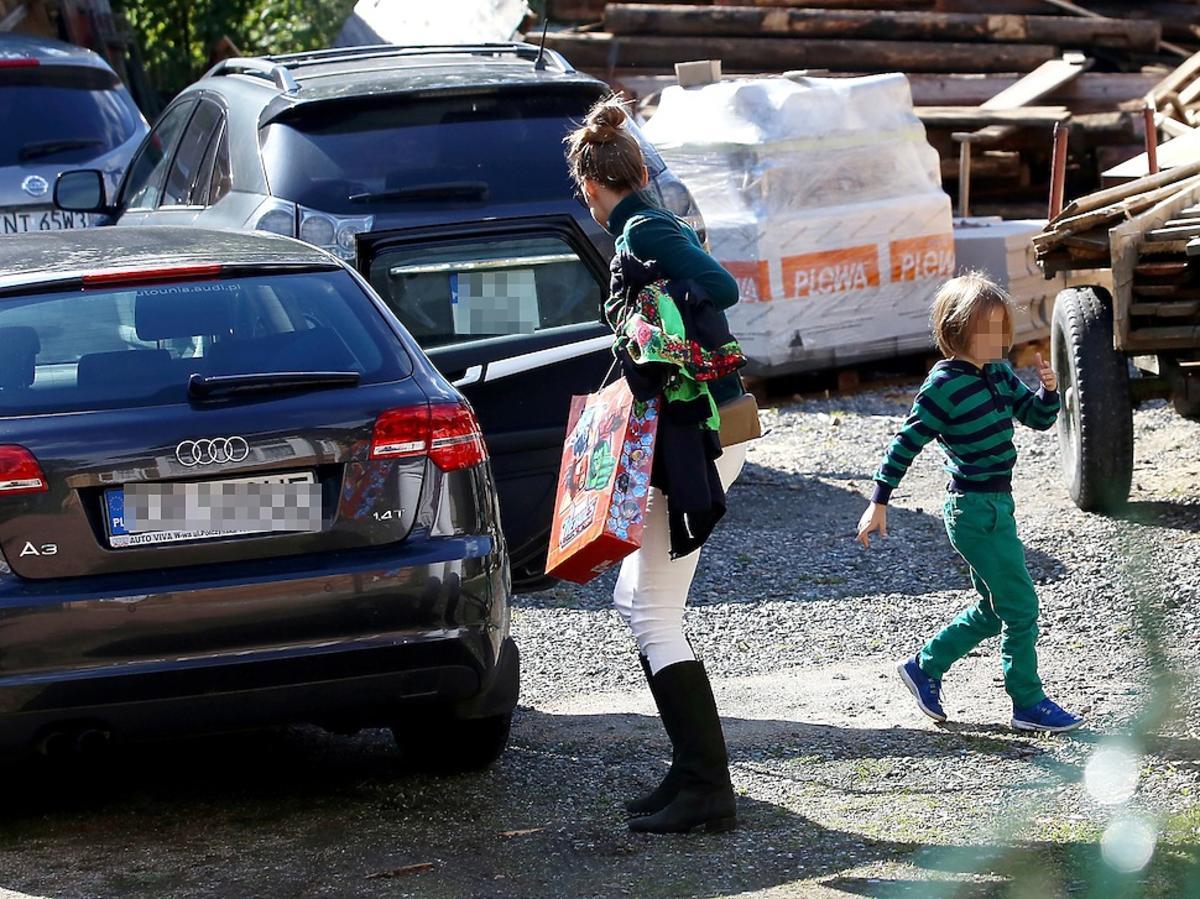 Alicha Bachleda-Curuś z upiętymi wlosami w kok i białych spodniach z synem na parkingu