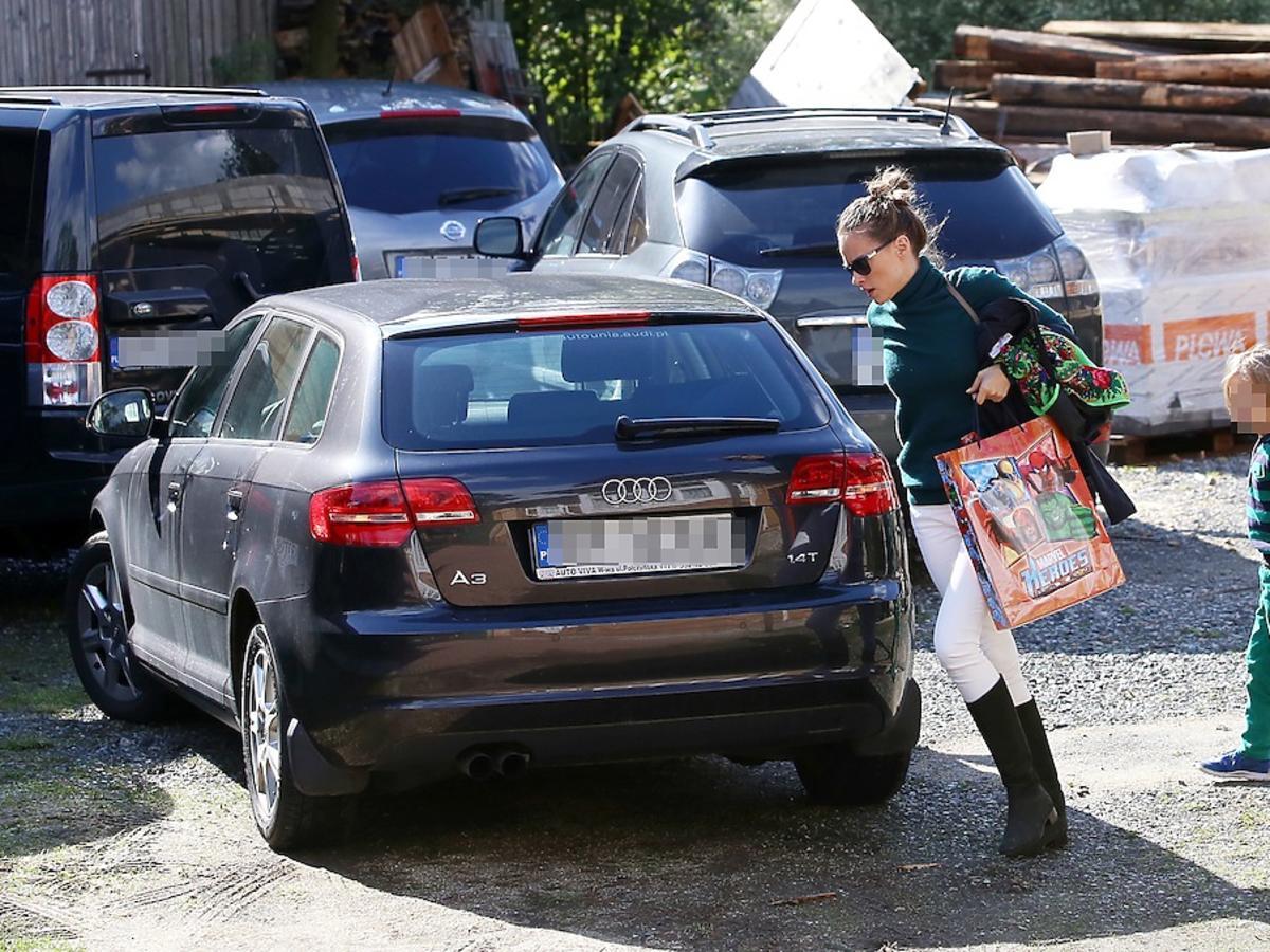 Alicja Bachleda-Curuś w białych spodniach i czarnych kozakach z synem kolo samochodu