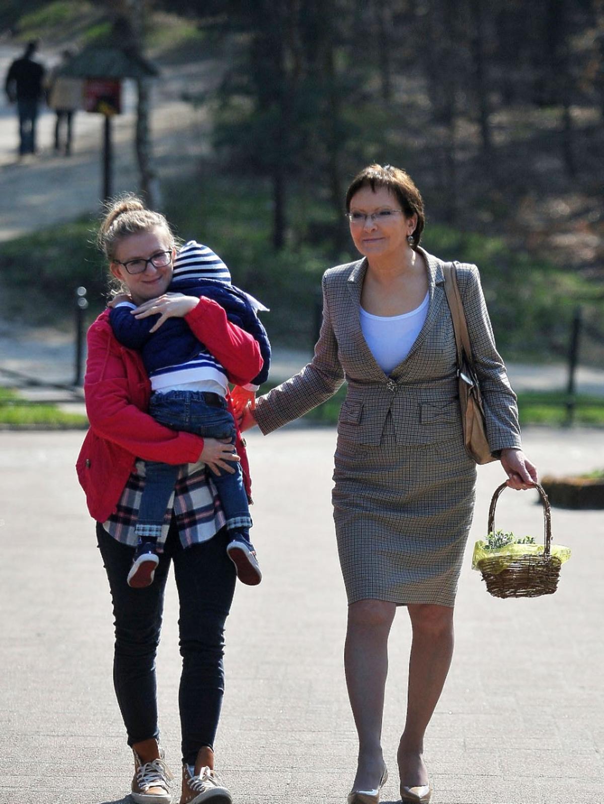Premier Ewa Kopacz z córką i wnukiem idą po chodniku ze święconką
