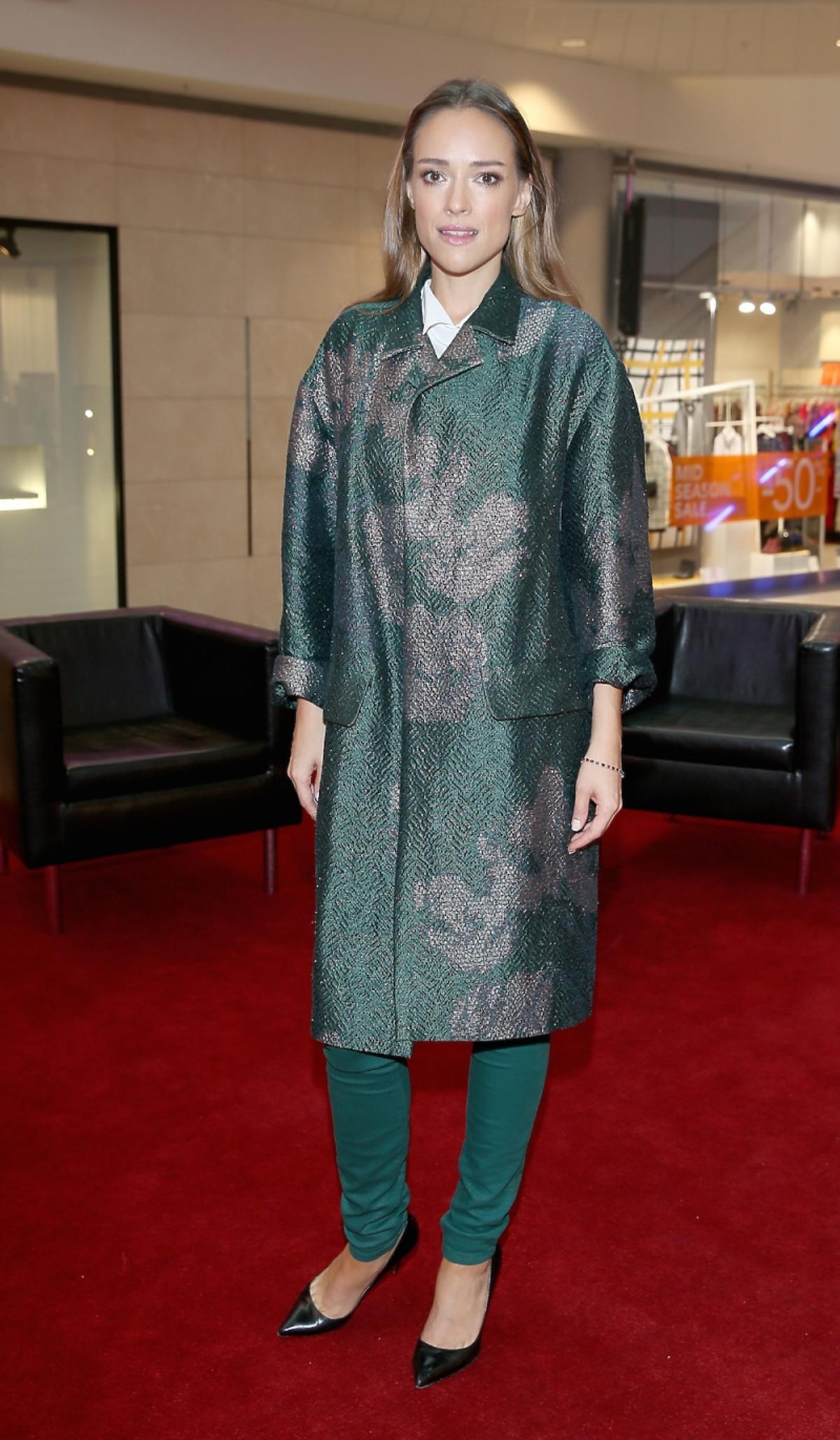 Alicja Bachleda-Curuś  w zielonych spodniach, wzorzystym płaszczu, białej koszuli, czarnych butach