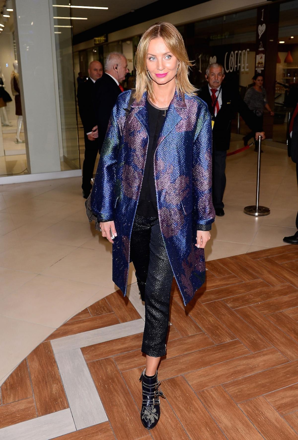 Agnieszka Szulim w czarnych błyszczących spodniach, niebieskim płaszczu błyszczącym, czarnym topie i czarnych butach z nitami i klamerkami