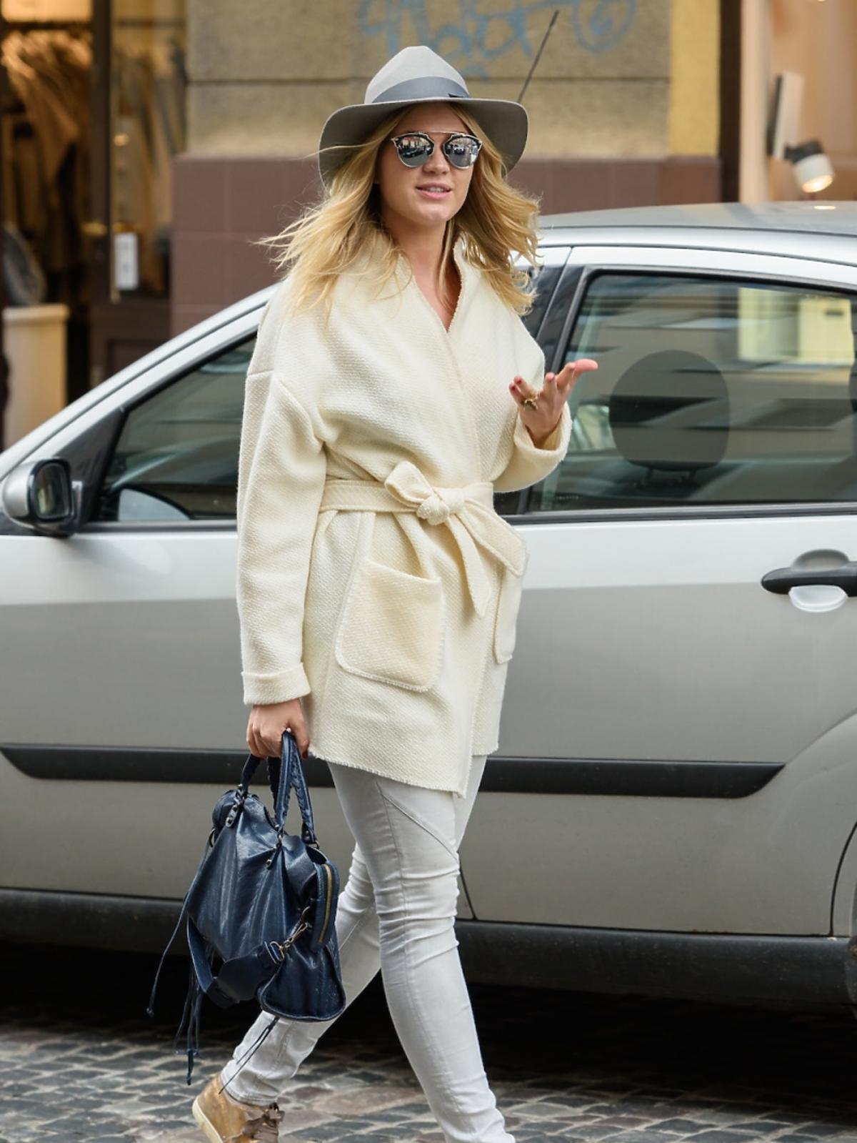 Zofia Ślotała w pastelowym płaszczu, szarym kapeluszu z dużym rondem, niebieską torbądo ręki, metalicznych butach, białych rurkach, okularach lustrzankach