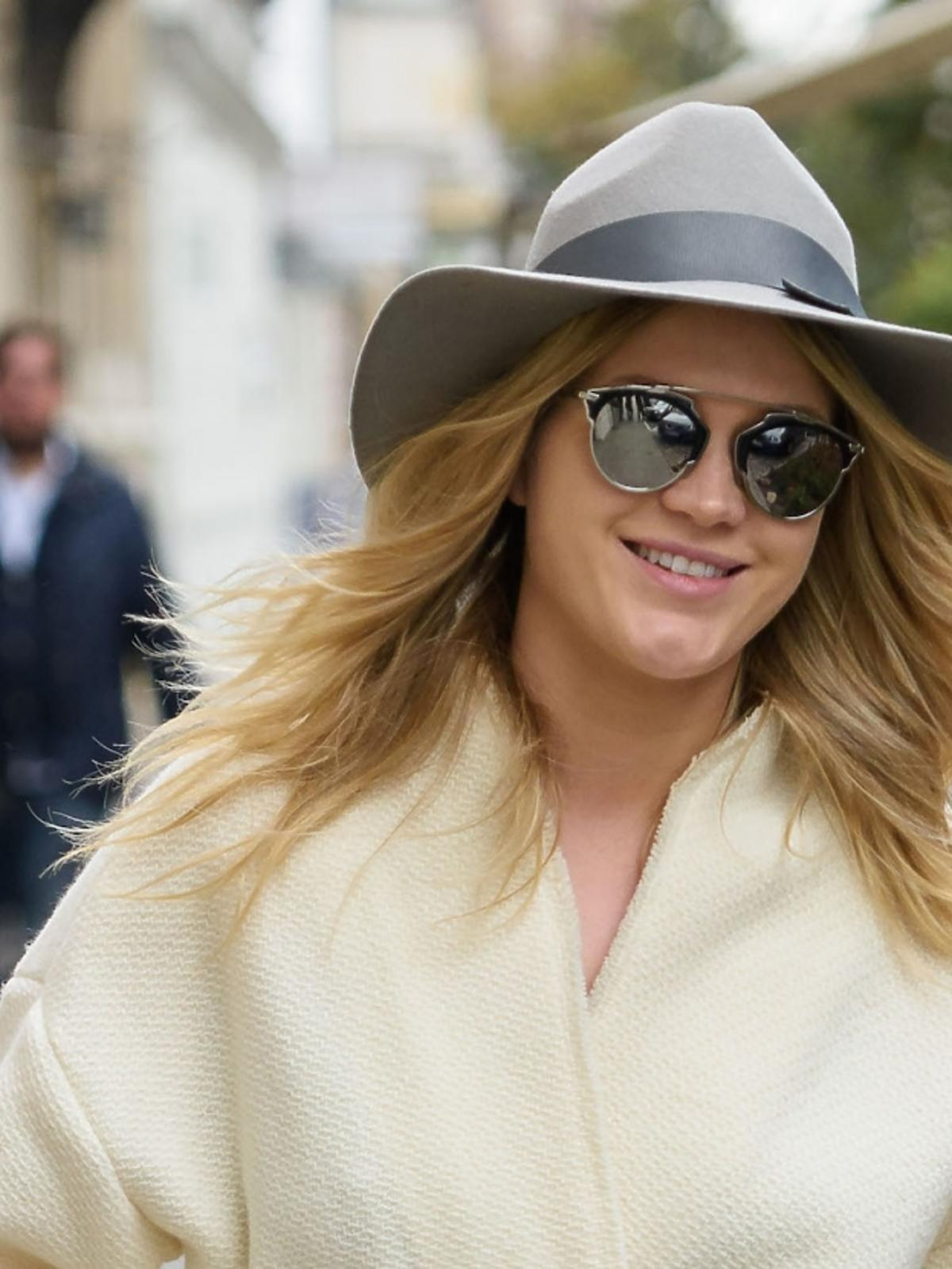 Zofia Ślotała w pastelowym płaszczu, szarym kapeluszu z dużym rondem, niebieską torbą do ręki, metalicznych butach, białych rurkach, okularach lustrzankach