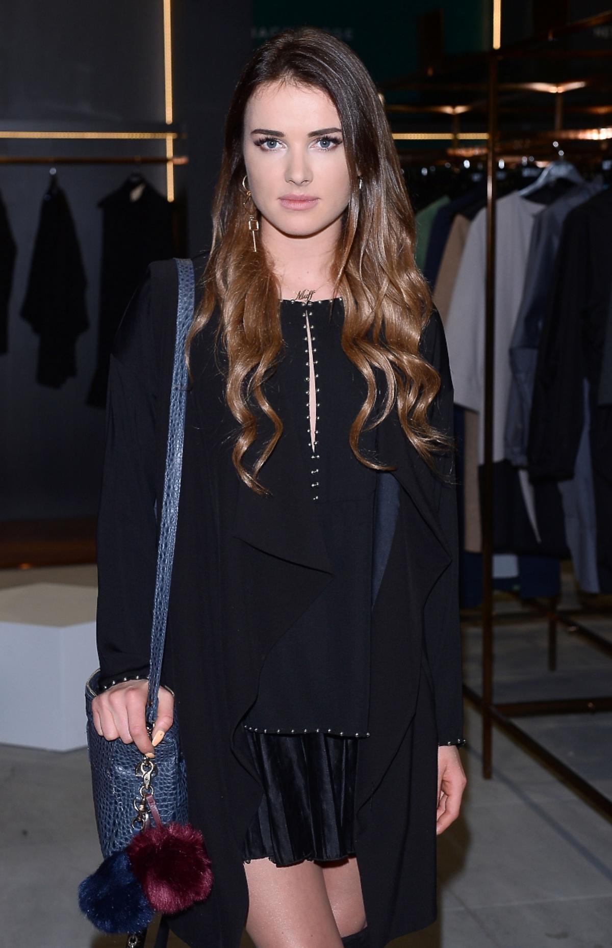 Maffashion w czarnej sukience, płaszczu w wysokich kozakach, z niebieską torbą na paski z pomponem