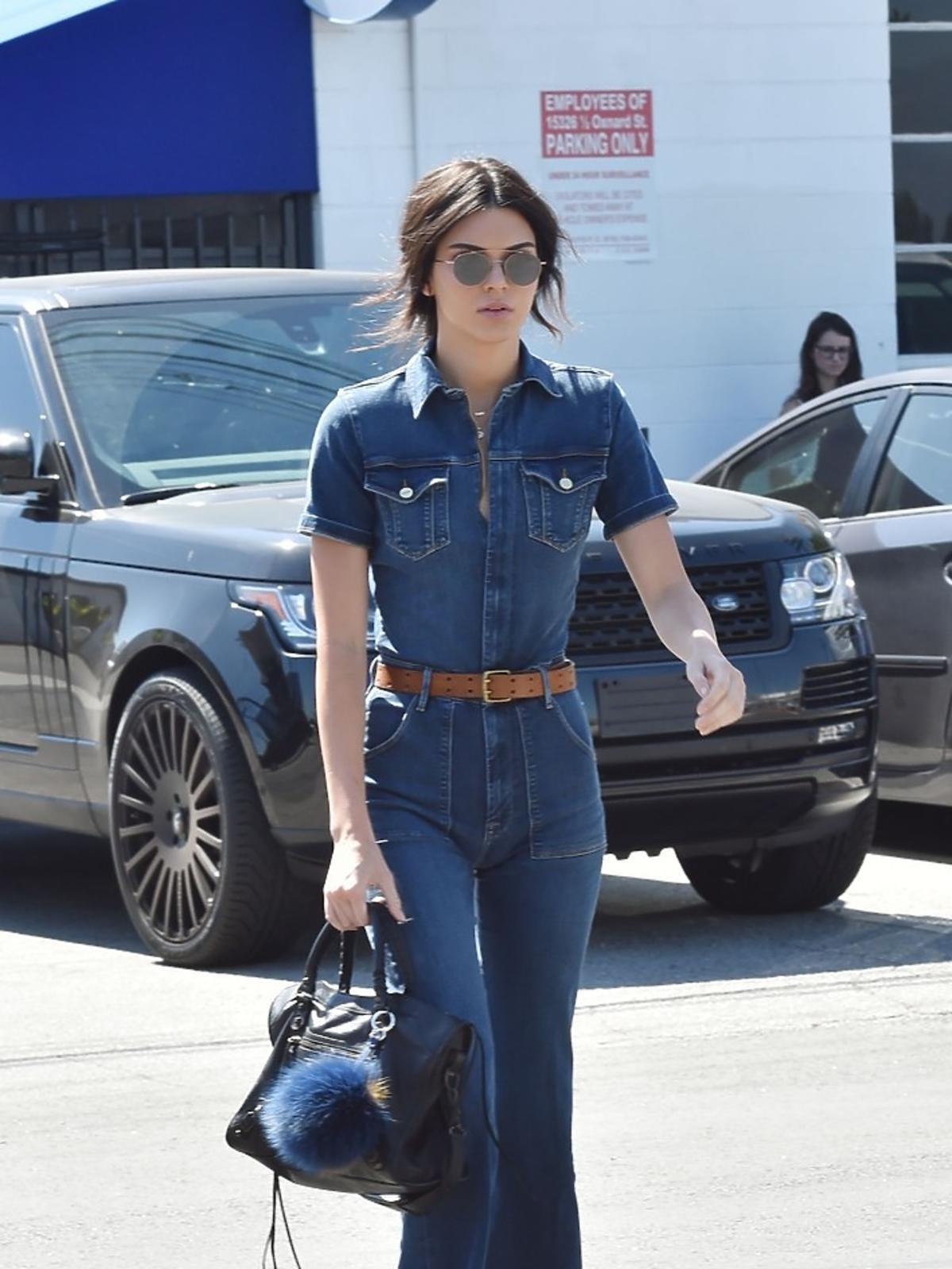 Kendall Jenner w dżinsowym kombinezonie, brązowych zamszowych botkach, w okularach, brązowym pasku z czarną torbą z pomponem