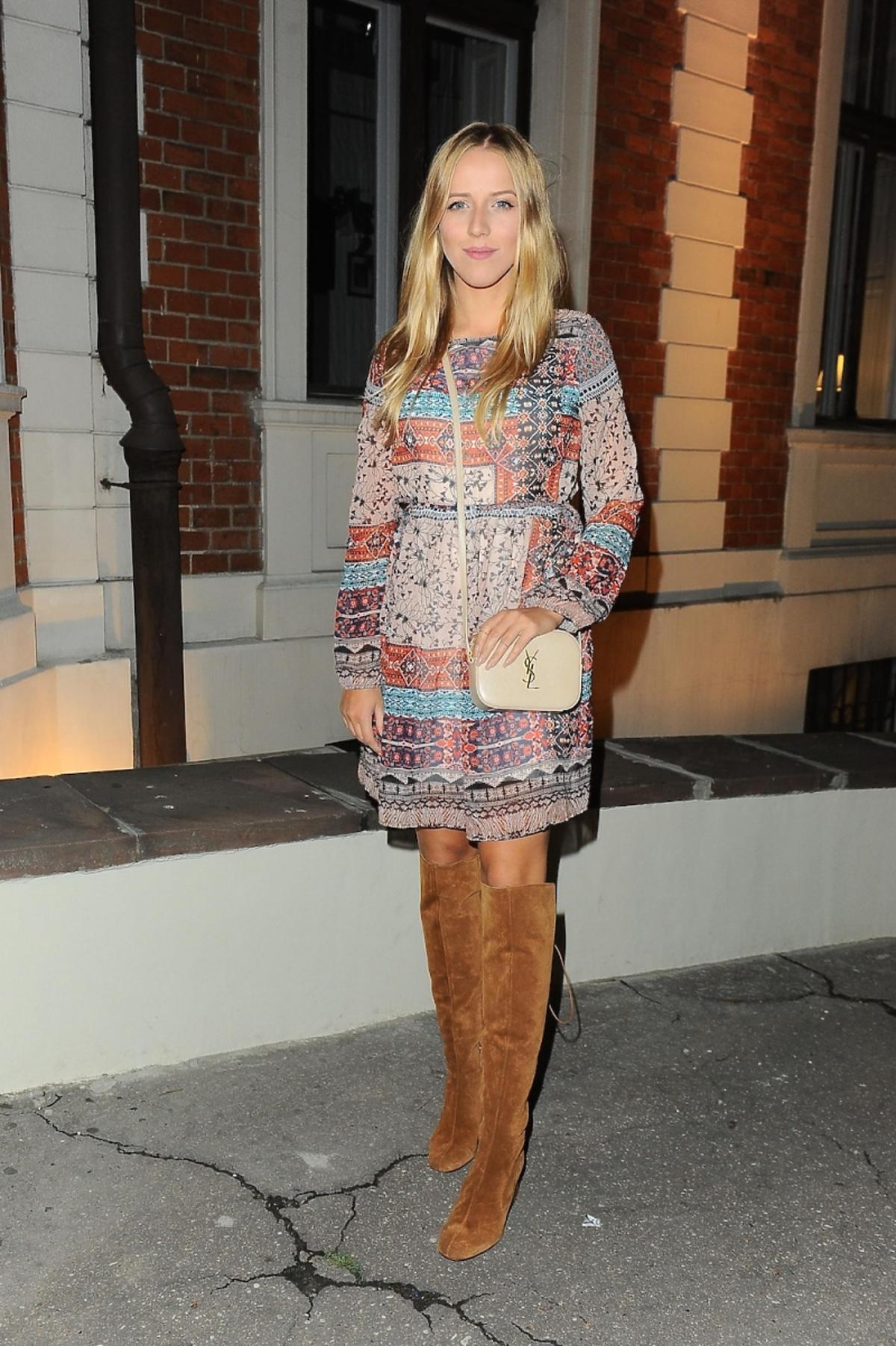 Jessica Mercedes w sukience w kolorowe printy, brązowych wysokich kozakach, małą kremową torebką na długim pasku