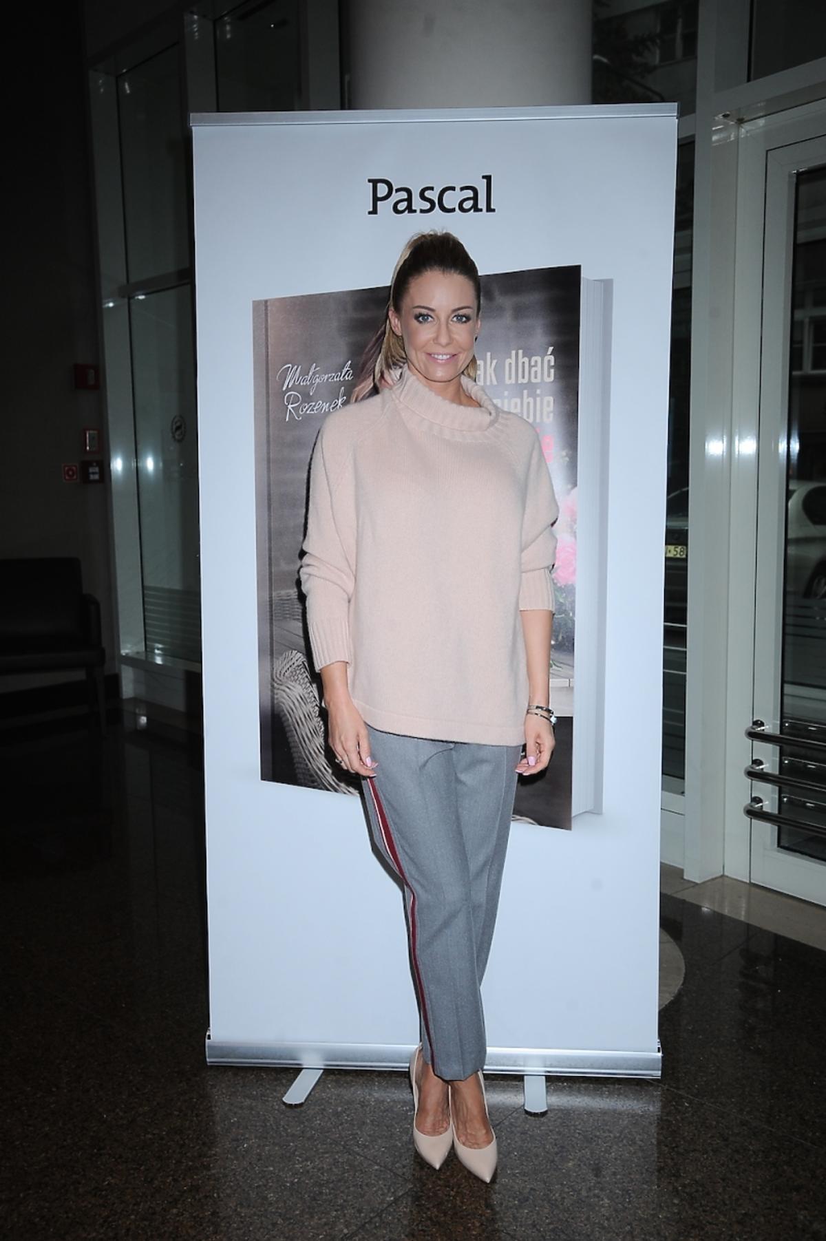 Małgorzata Rozenek w pastelowym różowym swetrze, szarych spodniach z lampasem, cielistych szpilkach