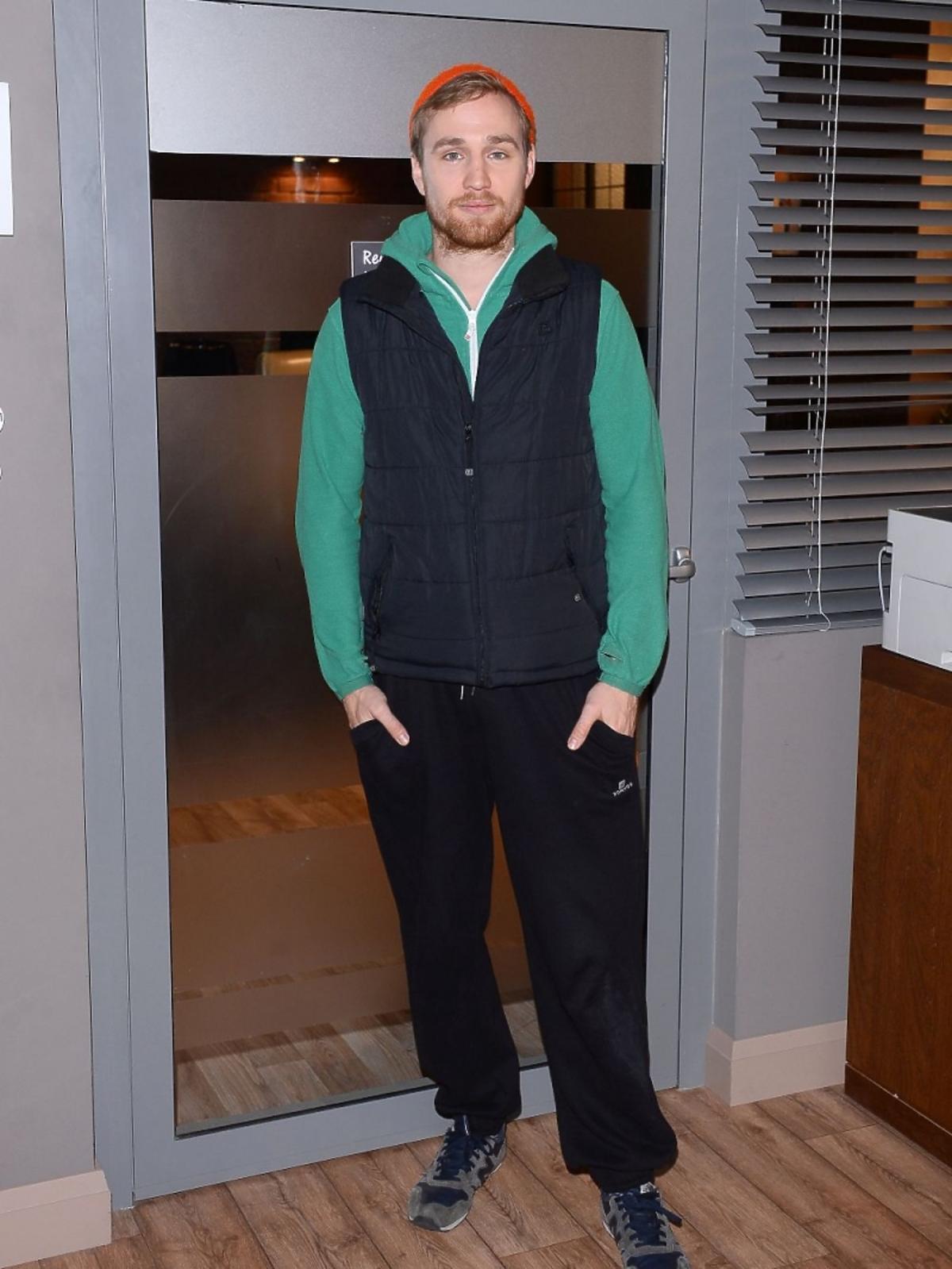 Mateusz Janicki w zielonej bluzie i czapce na planie serialu Singielka