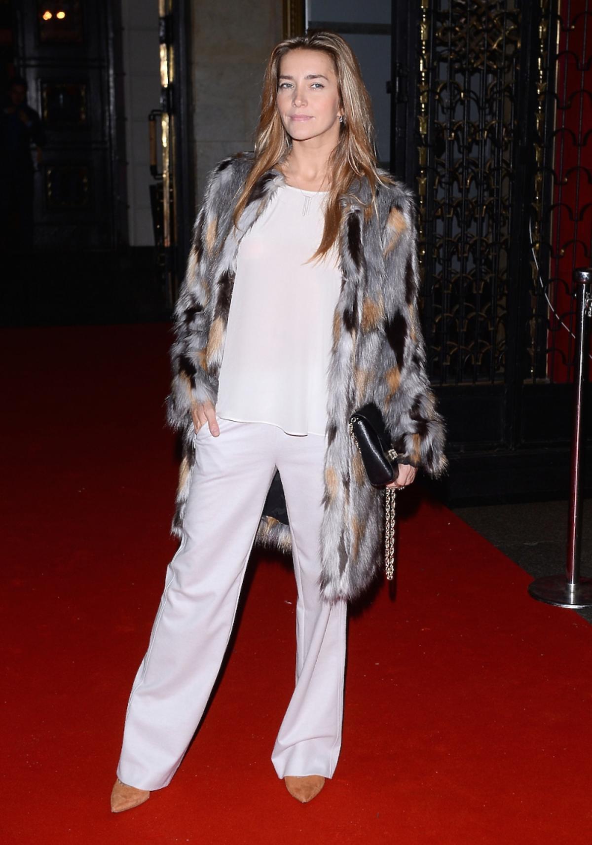 Kamilla Baar w białych spodniach, topie i kolorowym futerku z czarną toerbką na łańcuszku i  szpilki w kolorze naturalnej skóry