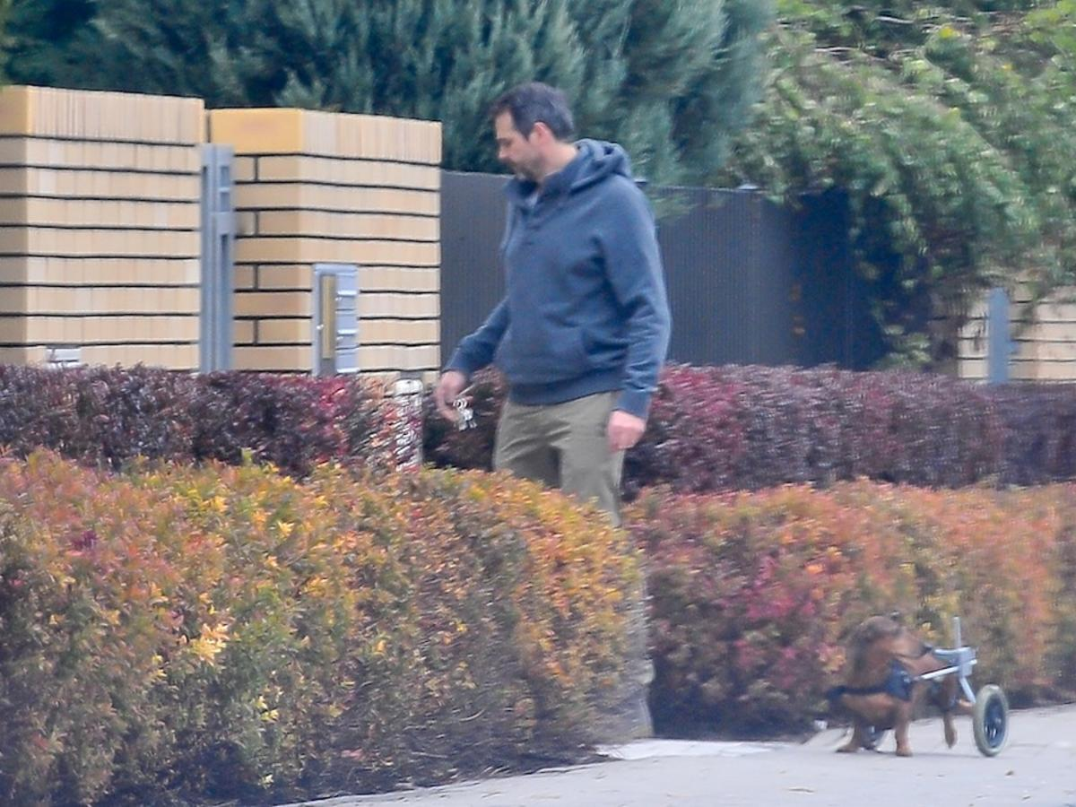 Paweł Deląg w dresie na spacerze w psem, który porusza się na wózku inwalidzkim