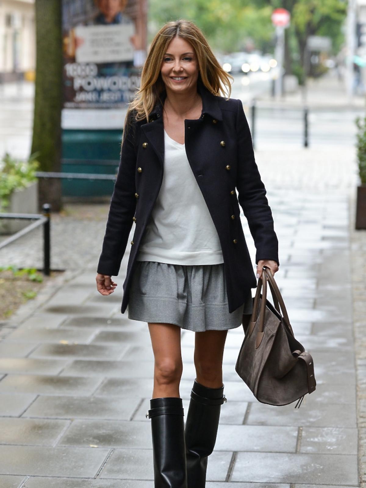 Rozenek w szarej spódniczce, białej bluzce, czarnym krótkim płaszczy ze srebrnymi guzikami, czarnych kozakach, z beżową torbą do ręki