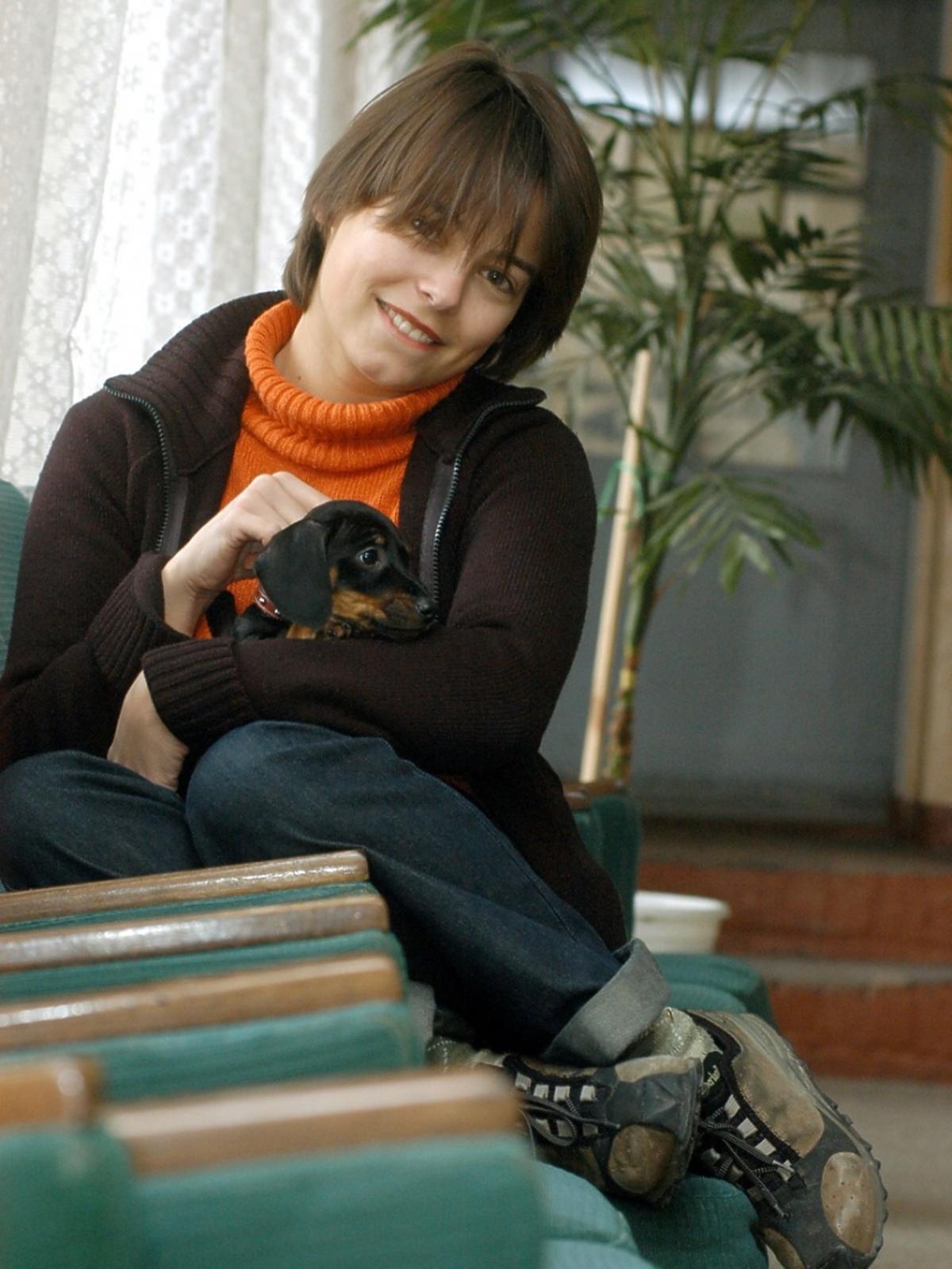 Anna Mucha siedzi i głaszcze psa