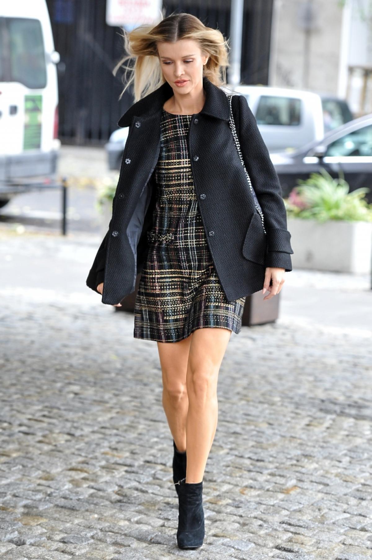 joanna Krupa w czarnym krótkim płaszczu z pikowanądużą torbą ozdobioną łańcuszkiem, sukience w kratę i czarnych botkach