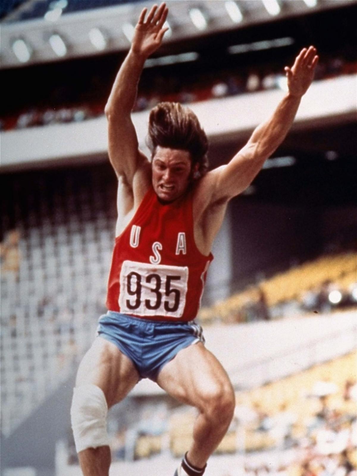 Bruce Jenner w trakcie skoku w dal, widać determinację na jego twarzy
