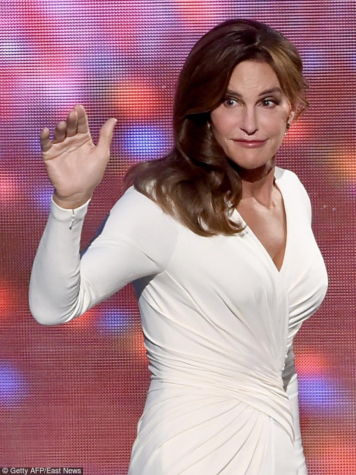 Wzruszona Caitlyn Jenner w białej, eleganckiej sukience, macha dłonią do widowni