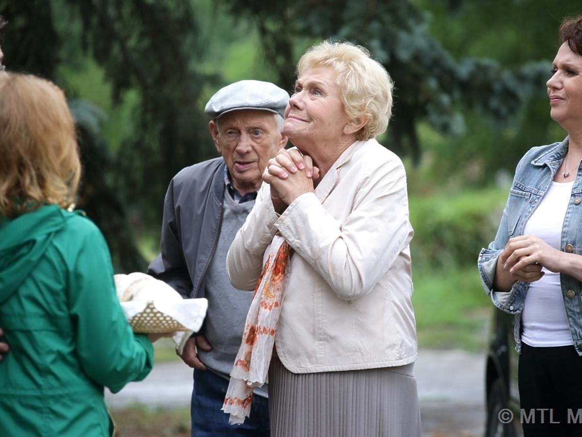Barbata w jasnym żakeicie i Lucjan Mostowiak w czapce cieszą się, że wracają do odnowionego domu w M jak Miłość