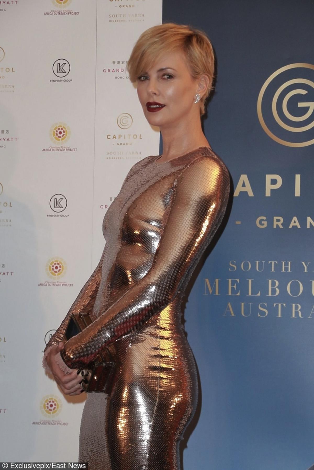 Charlize Theron w metalicznej złotej sukience z małą metaliczną torebką i czarnych sandałach na szpilce na czerwonym dywanie