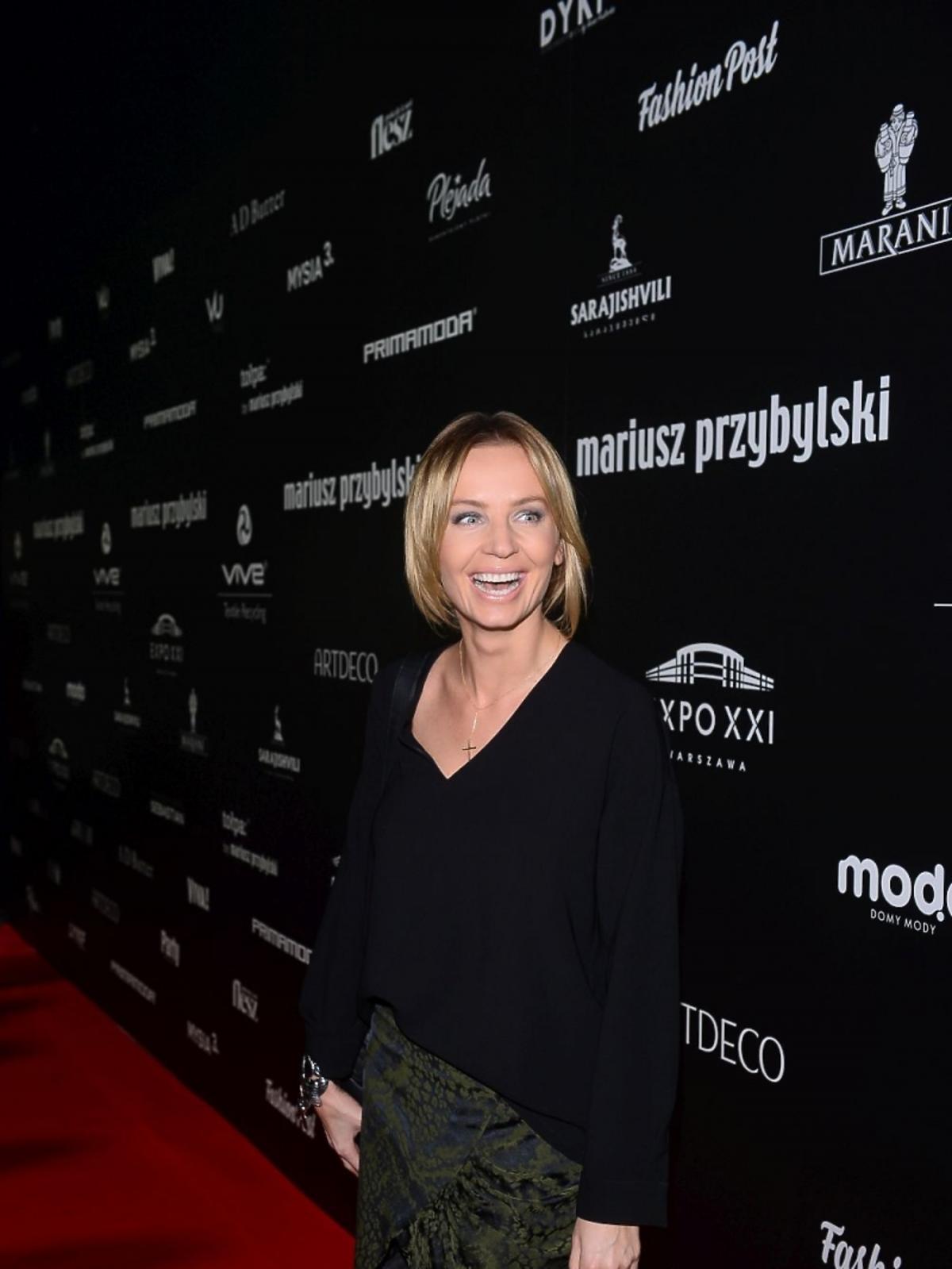 Agnieszka Szulim w czarnej bluzce i ciemnozielonej spódnicy
