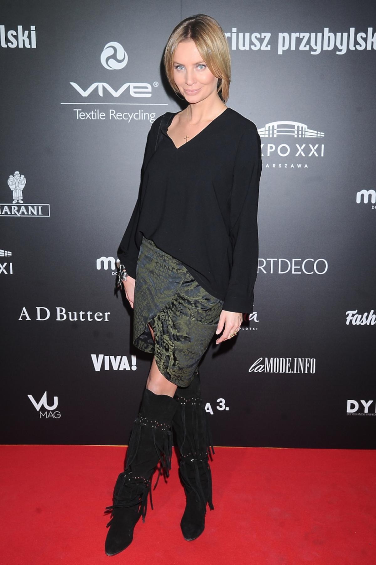Agnieszka Szulim w czarnej bluzce, wysokich kozakach z frędzlami, zielonej spódnicy