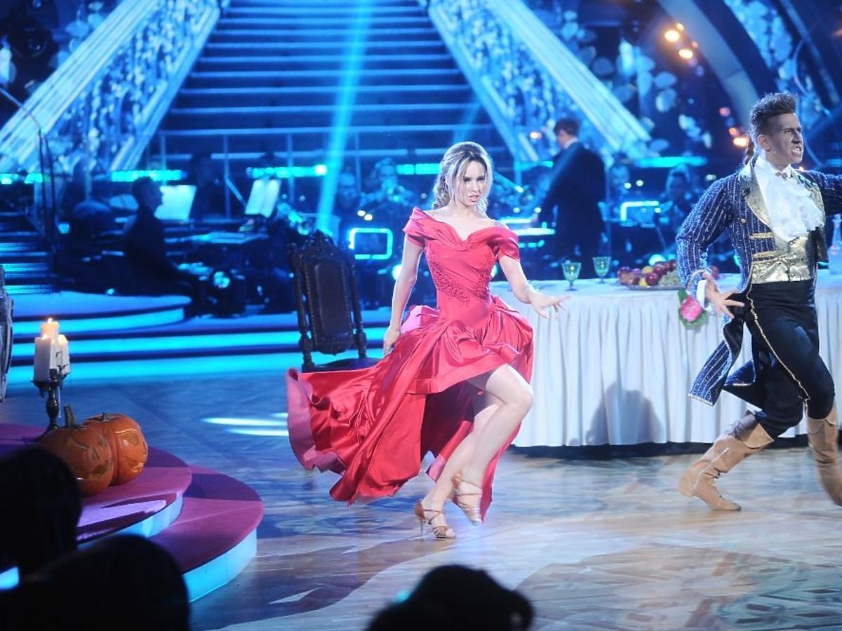 Ewelina Lisowska w czerownej sukni i Tomasz Barański we fraku i warkoczu tańczą w Tańcu z Gwiazdami