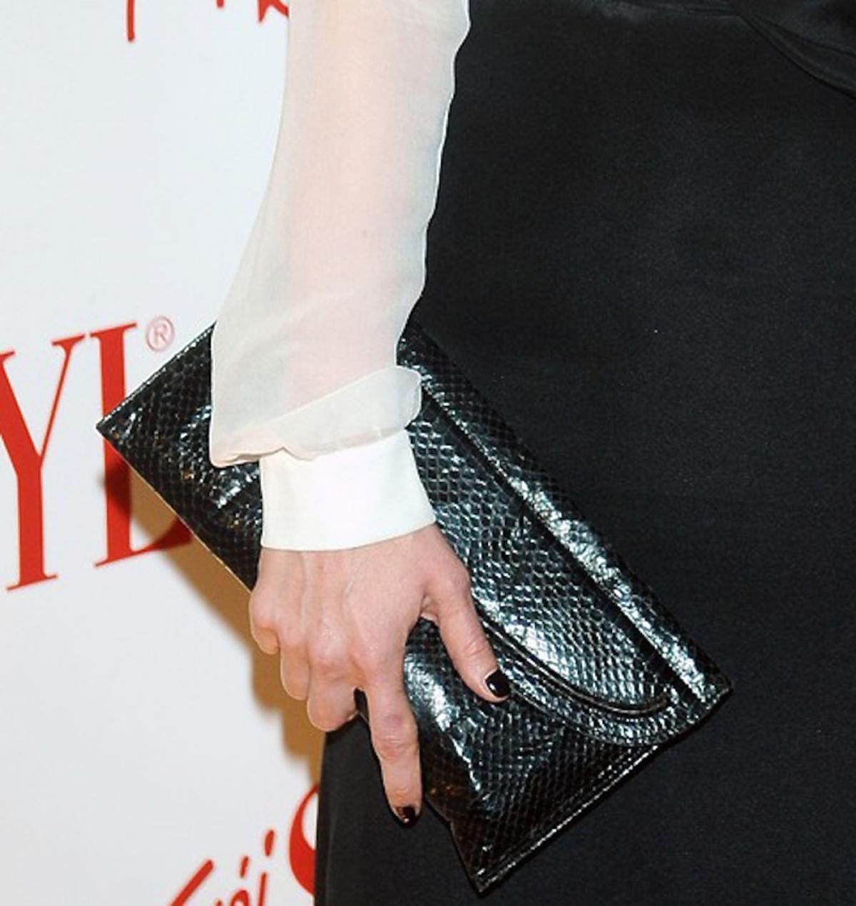 Katarzyna Warnke w białej transparentnej bluzce i czarnej spódnicy z czarną błyszczącą torebką