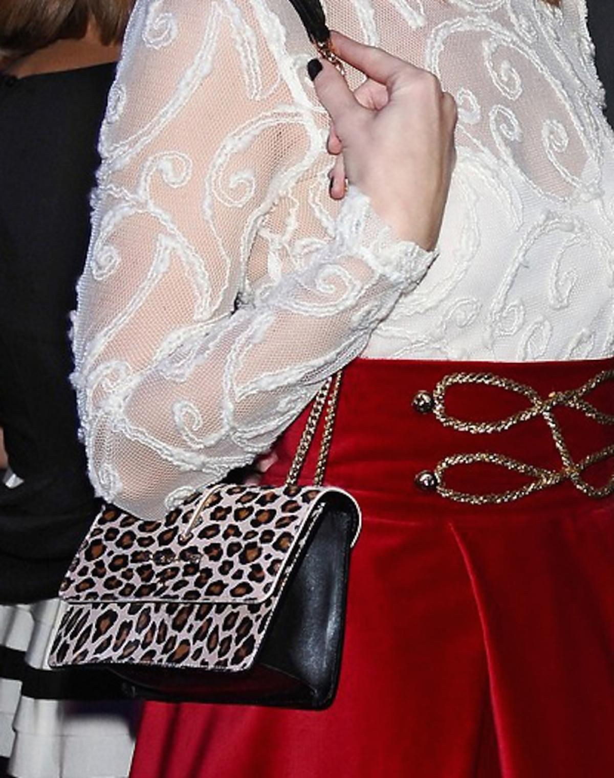 Halinki Mlynkowej w białej koronkowej bluzce, czerwonej spódnicy, celistych szpilkach z torbą w panterkę