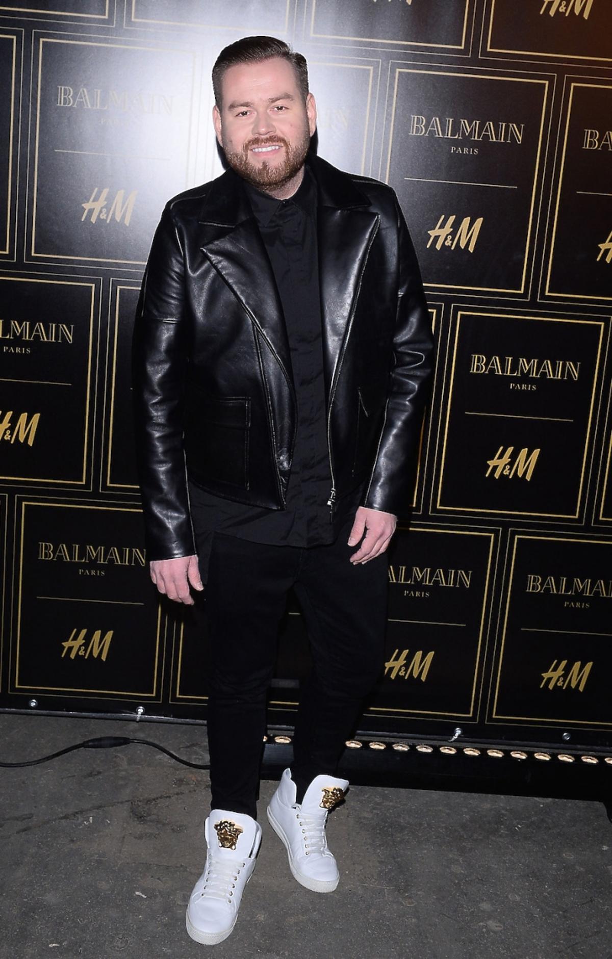 Tomasz Olejniczak w czarenj kurtce spodniach i białych butach ze złotą głową meduzy