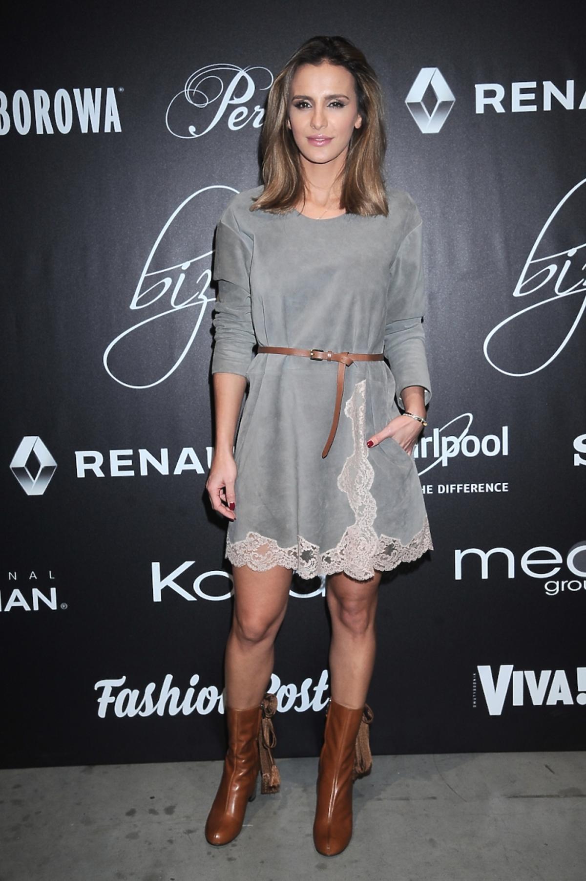 Sara Boruc w szraej sukience, brązowym pasku i botkach