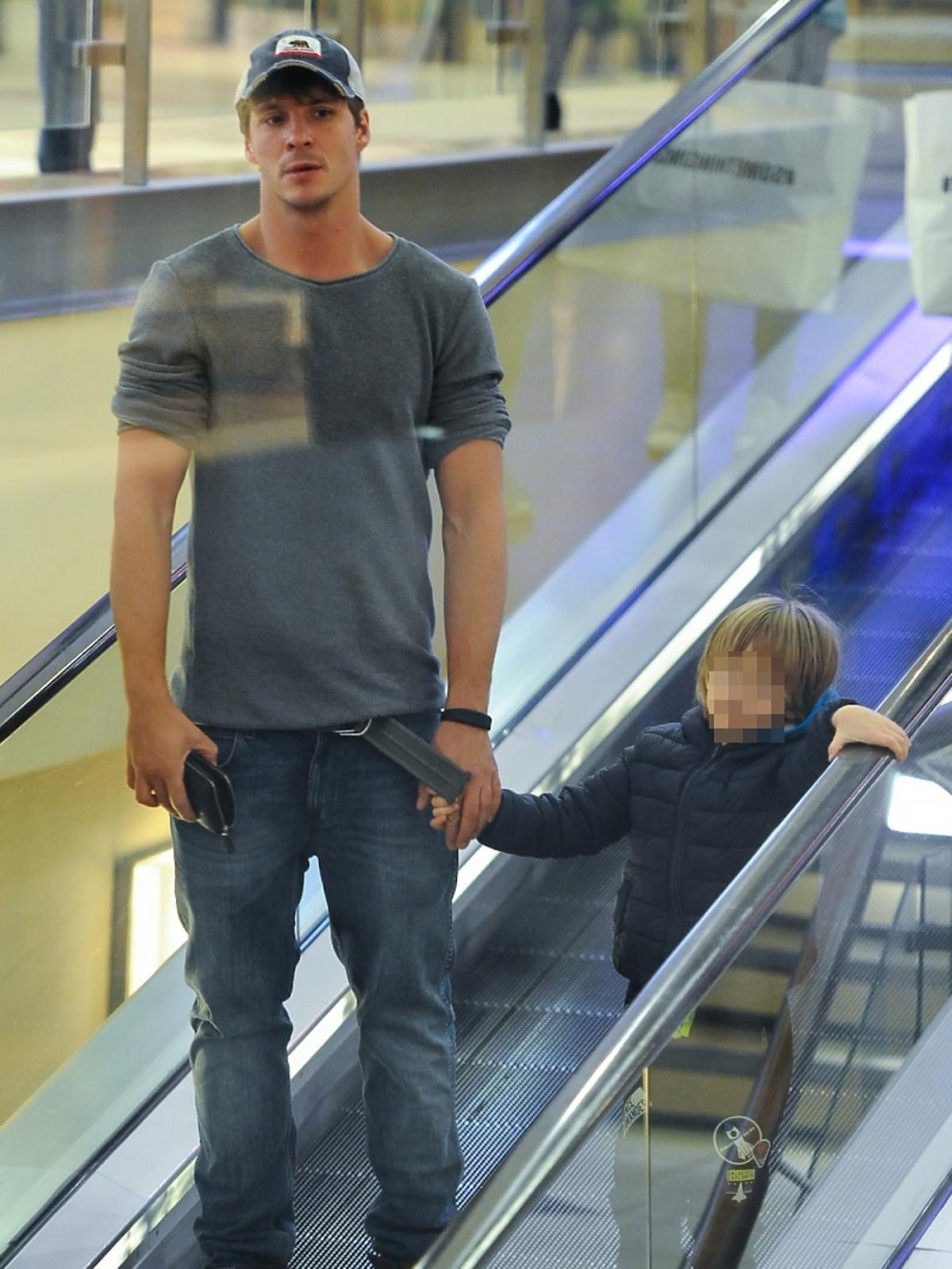 Mikołaj Roznerski na ruchomych schodach z synem Antosiem w centrum handlowym