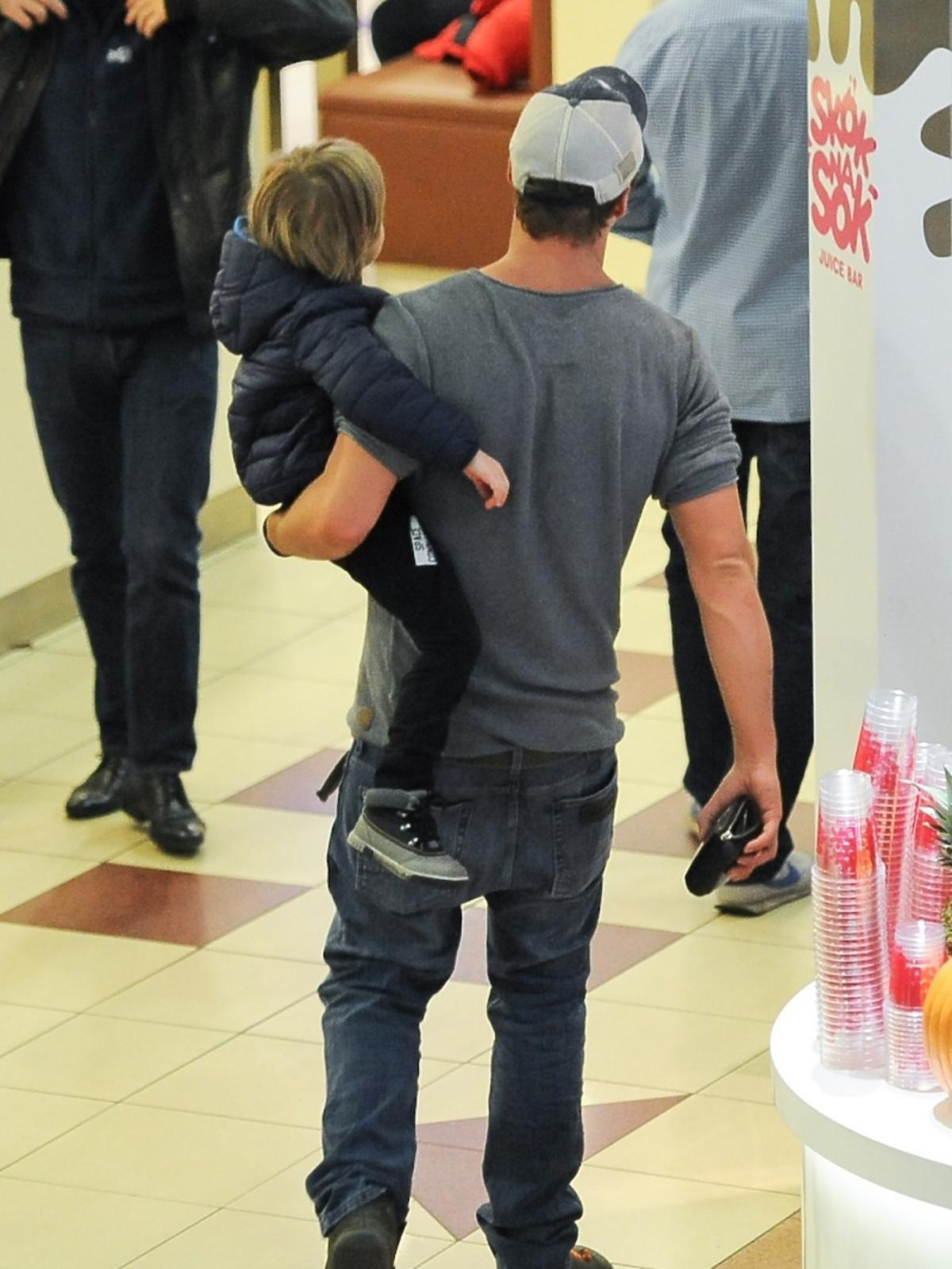 Mikołaj Roznerski niesie swojego czteroletniego syna Antosia w centrum handlowym