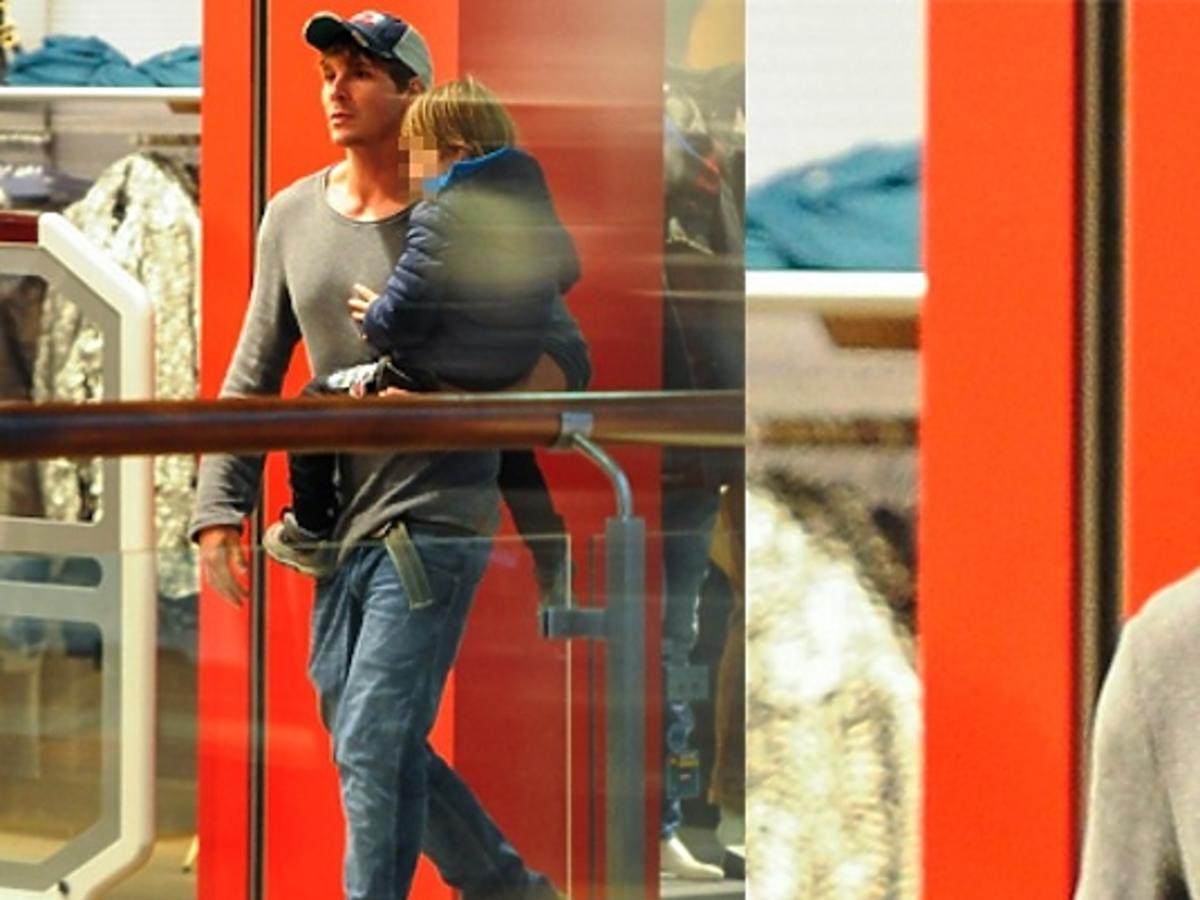 Mikołaj Roznerski w szarej bluzie z synem Antosiem w niebieskiej kurtce w centrum handlowym